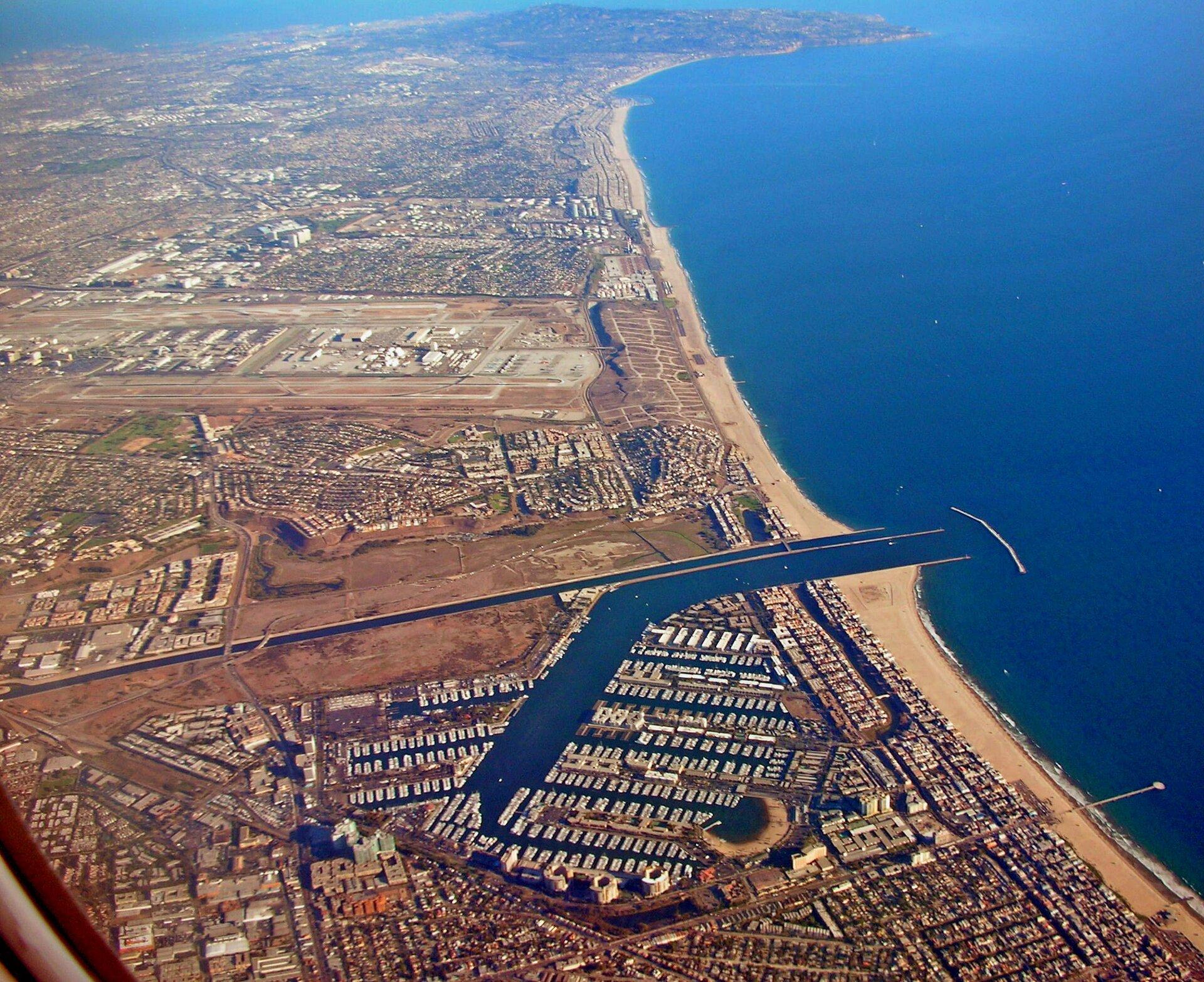 Na zdjęciu lotniczym gęsta zabudowa wmieście położonym nad morzem.