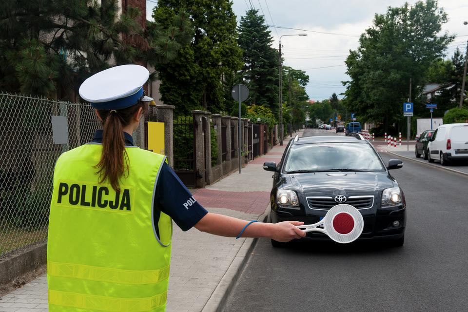 Zdjęcie przedstawia policjantkę zatrzymującą samochód do kontroli. Policjantka ustawiona jest tyłem do obserwatora zdjęcia, wwyciągniętej prawej ręce ma czerwony lizak. Zatrzymywany samochód to elegancka toyota wciemnych barwach. Miejsce akcji to niezbyt ruchliwa droga wdzielnicy willowej.