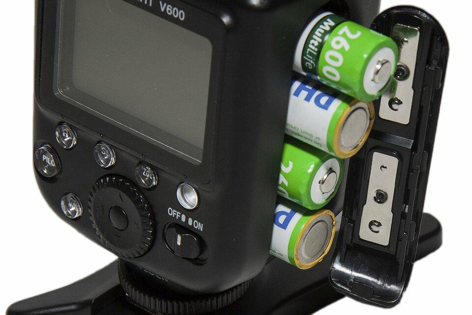 Zdjęcie przedstawia zbliżenie korpusu zewnętrznej lampy błyskowej dla aparatu fotograficznego. Urządzenie jest czarne, na tylnej ściance ma wyświetlacz LCD iprzyciski sterujące. Komora zasilania zprawej strony jest otwarta, wystają zniej cztery akumulatorki formatu AA, czyli popularne paluszki, ułożone wjednym szeregu. Naprzemiennie wystają końcówki biegunowe plus iminus. Na klapce zamykającej znajdują się dwie blaszki, których zadaniem jest zwieranie par baterii wszereg.