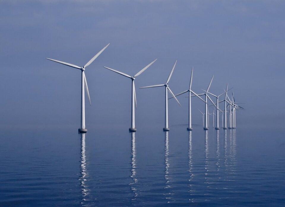 Na zdjęciu kilkanaście turbin wiatrowych stojących wwodzie.