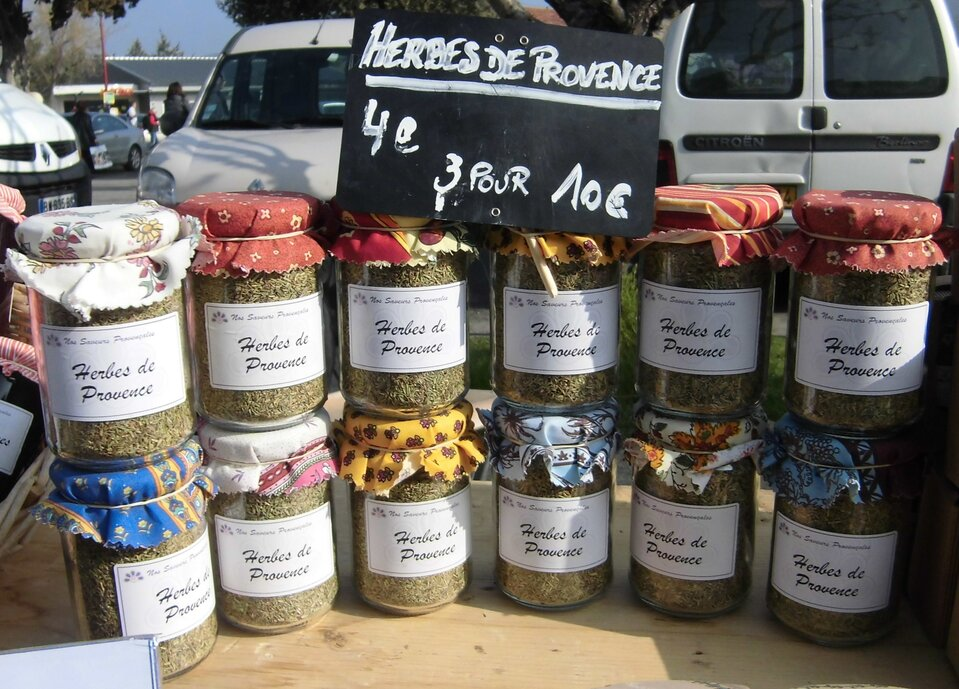 Na zdjęciu kilkanaście słoików zprzyprawami, zioła prowansalskie, kolorowe tkaniny na wieczkach.