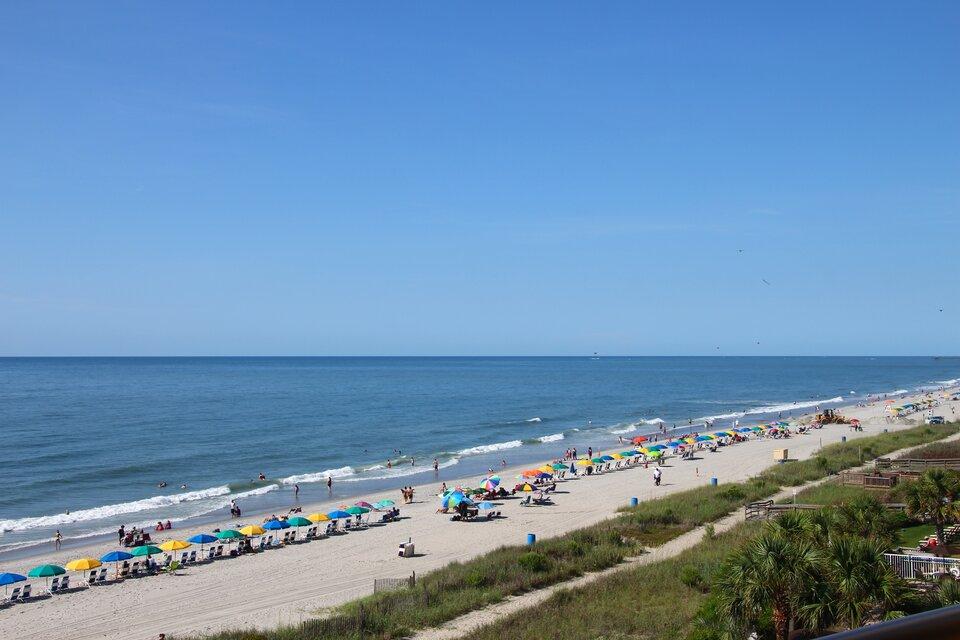 Na zdjęciu płaska, piaszczysta plaża wzdłuż brzegu morza. Leżaki, kolorowe parasole.