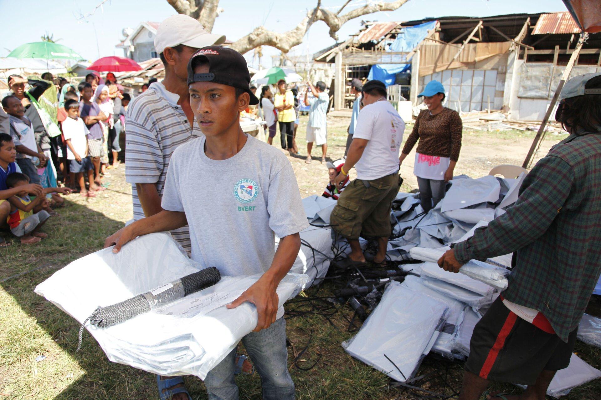 Na zdjęciu kolejka osób woczekiwaniu na pomoc humanitarną. Na pierwszym planie osoby, które otrzymały już namioty.