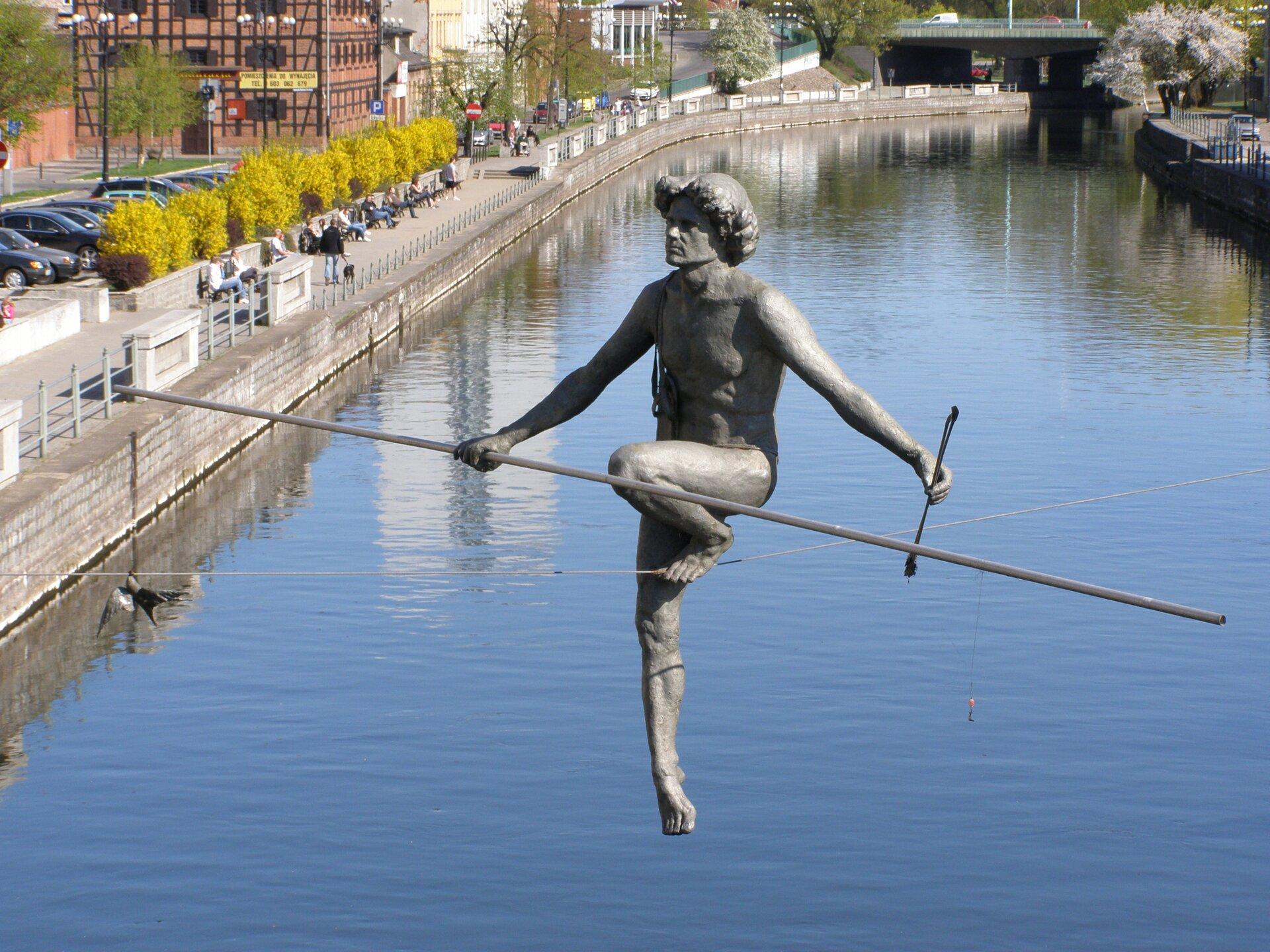 """Ilustracja przedstawia rzeźbę Jerzego Jotki Kędziory pt. """"Przechodzący"""". Rzeźba obrazuje nagiego mężczyznę przechodzącego po linie zawieszonej pomiędzy dwoma brzegami rzeki. Mężczyzna wprawej dłoni trzyma długi kij, pomagający mu zachować równowagę. Wlewej dłoni trzyma strzałę."""