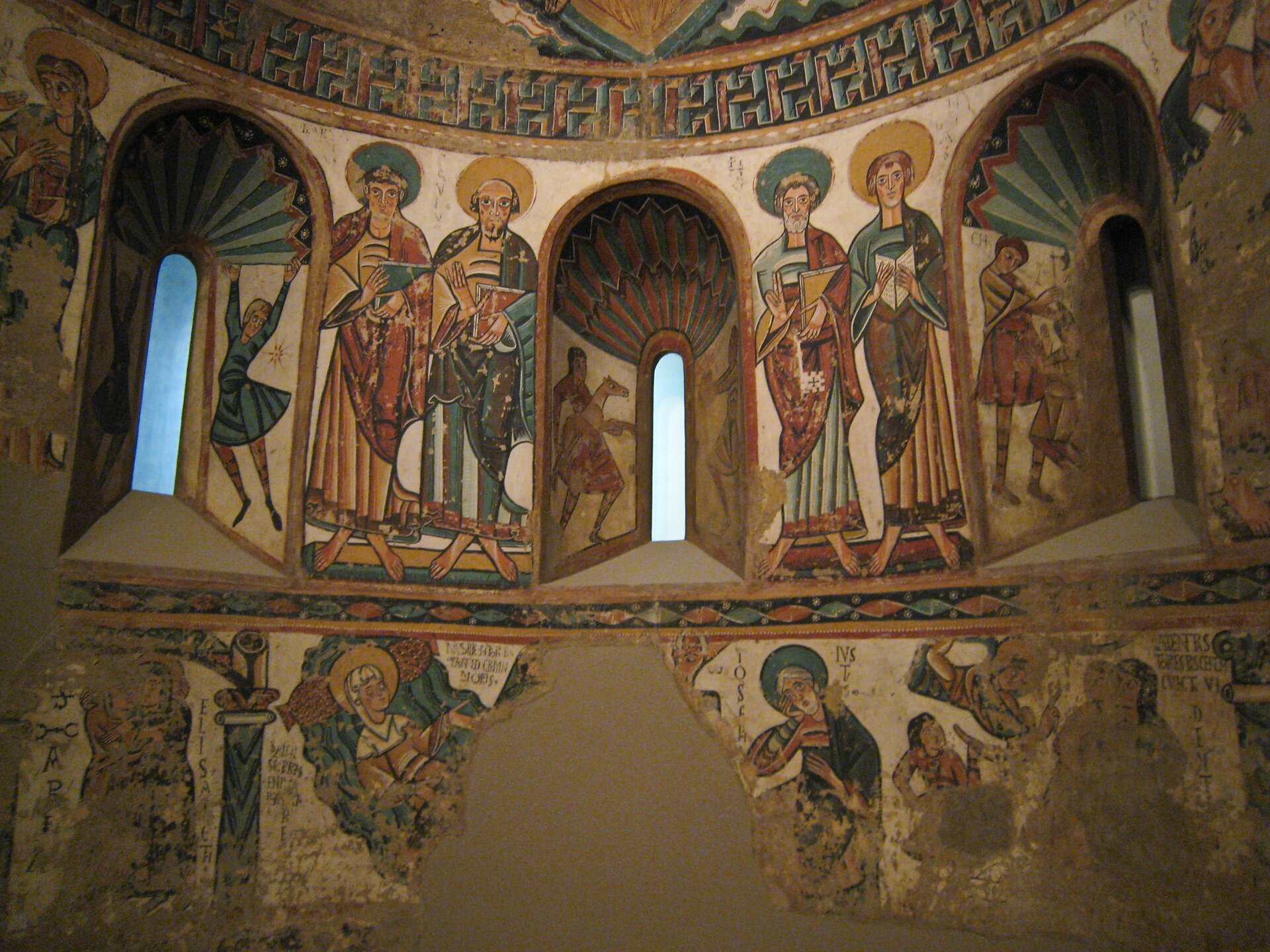 """Ilustracja interaktywna przedstawia malowidło """"Chrystus Chwalebny isymbole czterech ewangelistów"""", znajdujące się wMuzeum Sztuk Pięknych wBostonie wStanach Zjednoczonych. Na zdjęciu ukazane jest wnętrze ztrzema małymi, podłużnymi oknami zwieńczonymi łukami. Ściany pokryte są freskami ogrubym, czarnym konturze, które skomponowane są wtrzech pasach oddzielonych ornamentami. Dolny, najgorzej zachowany pas zwieloma ubytkami, przedstawia sceny biblijne. Nad nim znajduje się pas zoknami, pomiędzy którymi umieszczone zostały wparach postacie świętych. Również wnęki okienne zostały pokryte malowidłami zpostaciami iornamentyką. Przedstawione freski odznaczają się niezwykle bogatą kolorystyką. Dominującymi barwami są: biel, ciepła żółć, czerwień ibłękit."""