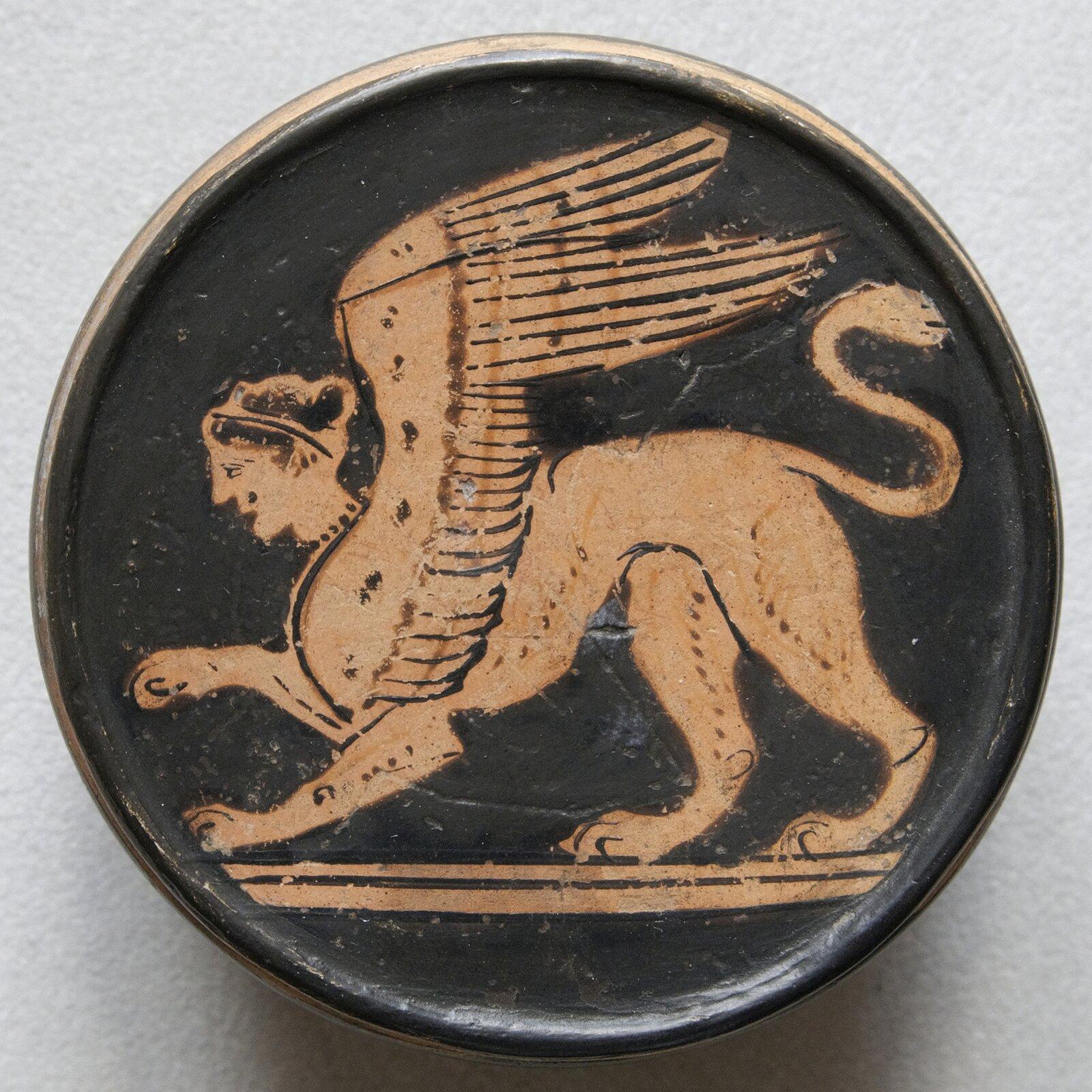 lustracja przedstawia fotografię obrazujące malarstwo na naczyniu. Malunek przedstawia wizerunek Sfinksa przechadzającego się po płaskiej powierzchni. Sfinks posiada głowę kobiety oraz ciało lwa, atakże duże skrzydła. Sfinks został przedstawiony na czarnym tle.