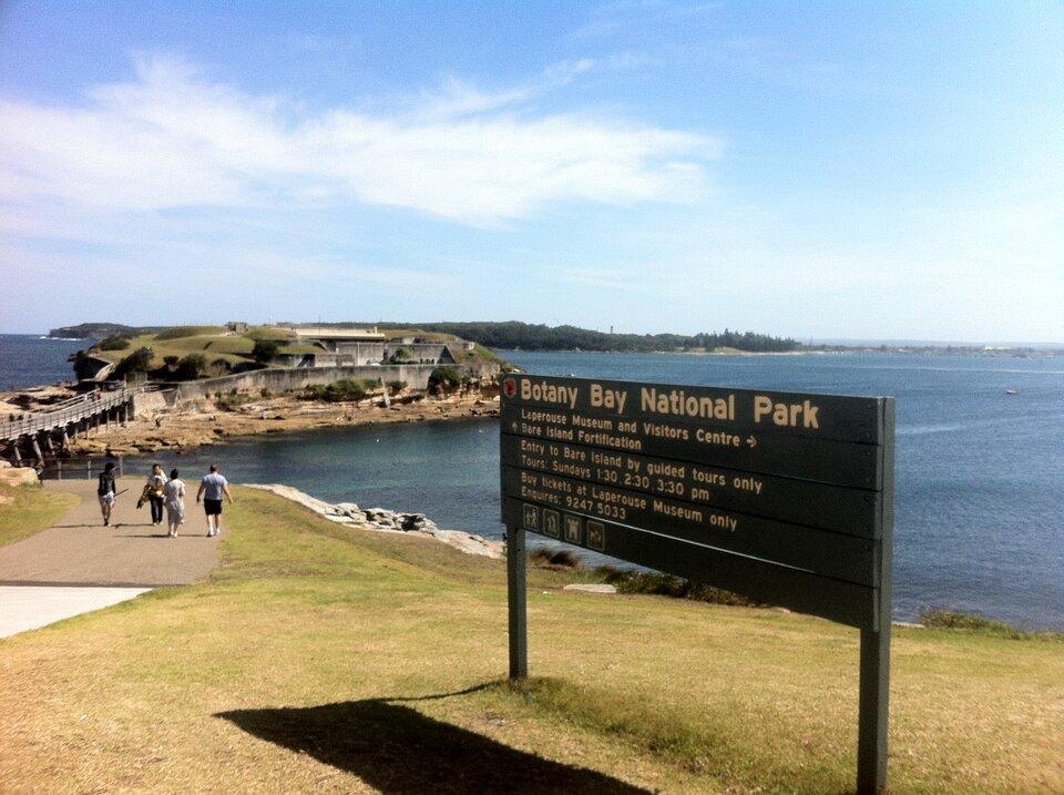 Na zdjęciu brzeg zbiornika wodnego, cypel, na który prowadzi wąski mostek. Na brzegu tablica informacyjna.