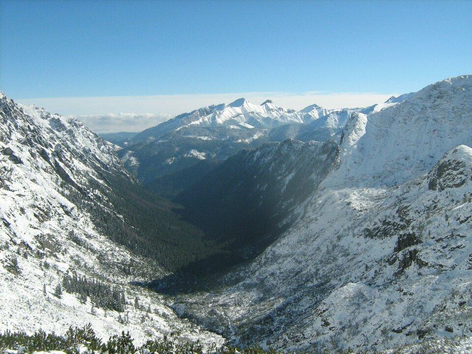 Fotografia prezentuje ośnieżone stoki górskie, które otaczają dookoła dolinę.