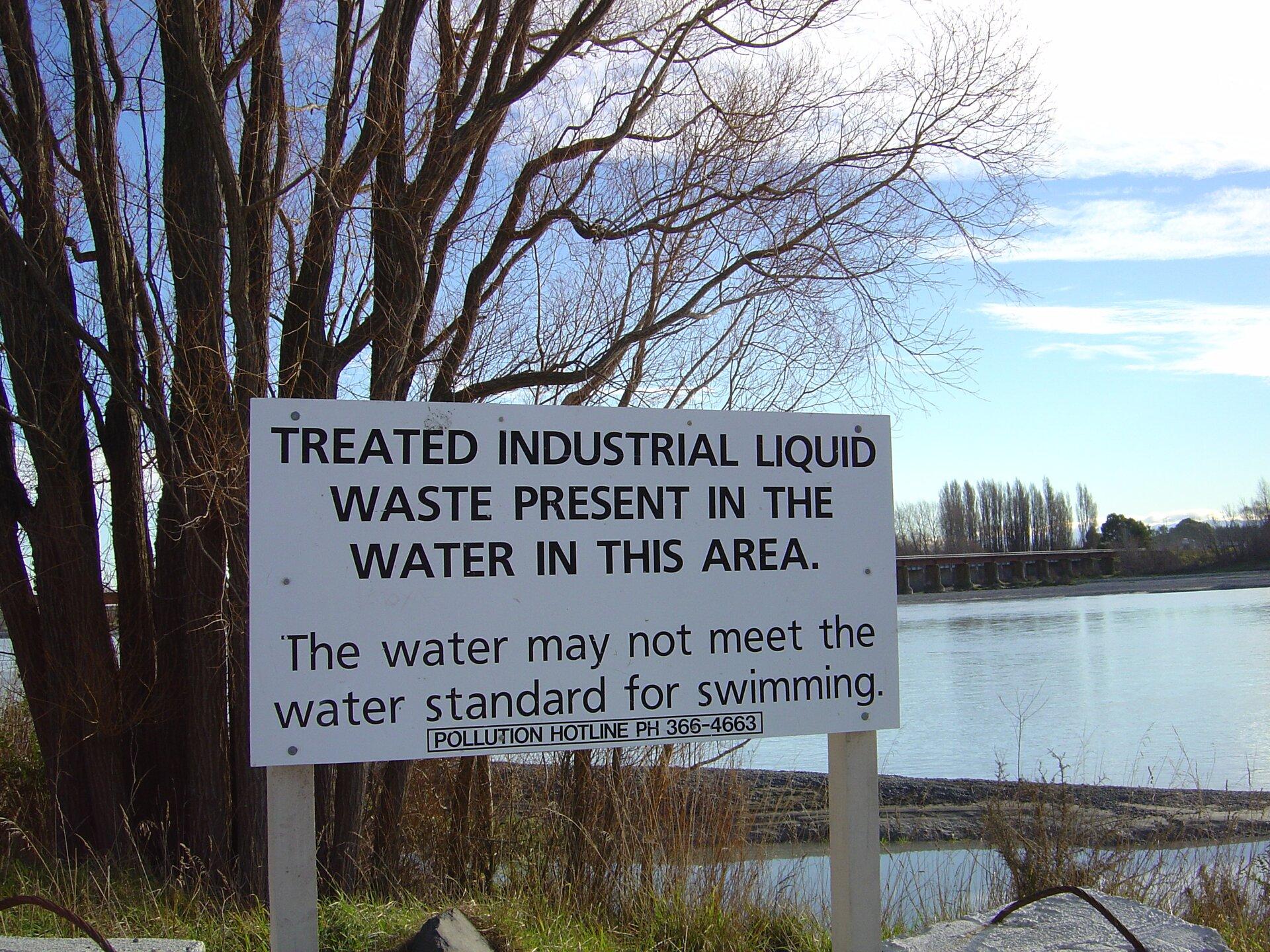 Na zdjęciu brzeg rzeki, krzewy. Na pierwszym planie tablica informacyjna. Czarny napis na białym tle. Informuje ozanieczyszczeniu wody.