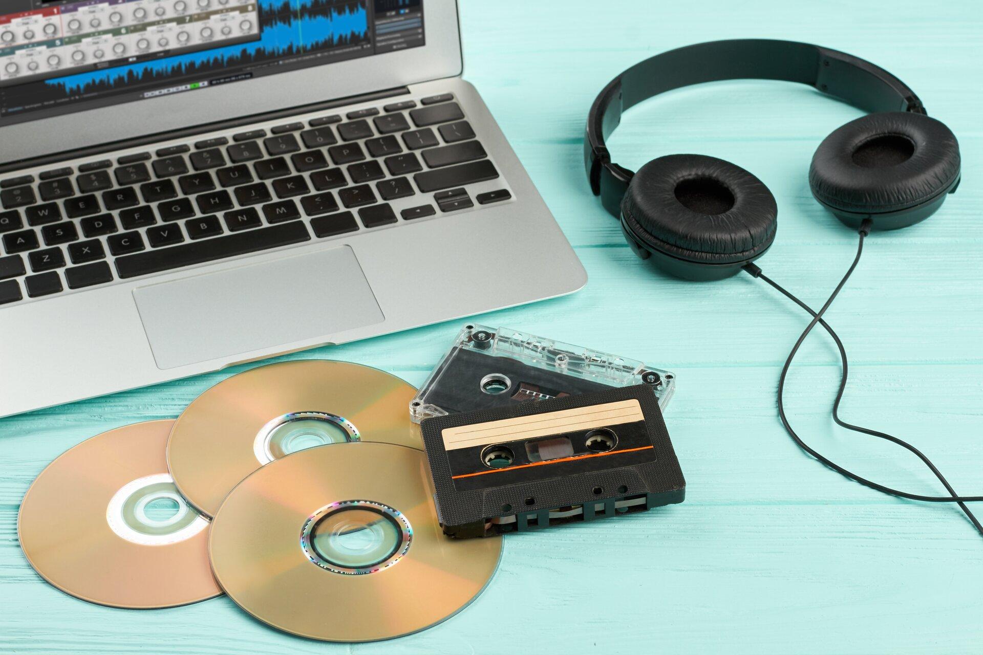 Zdjęcie ukazuje urządzenia do odtwarzania muzyki: dwie kasety magnetofonowe, trzy płyty CD, czarne słuchawki oraz laptop.