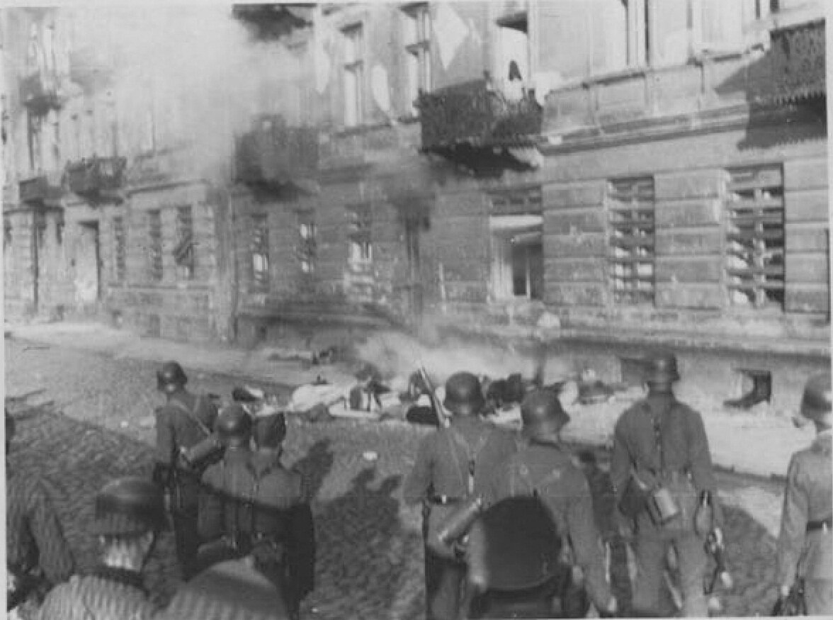 Niemieccy żołnierzeoglądający ciała ofiar samobójczych skoków zwysokich pięter Niemieccy żołnierzeoglądający ciała ofiar samobójczych skoków zwysokich pięter Źródło: Autor nieznany, domena publiczna.