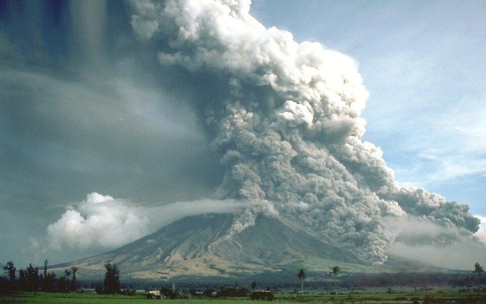 Na zdjęciu mieszanina gazów wulkanicznych ipopiołów unosząca się nad wzniesieniem. Na pierwszym planie zabudowania inieliczne drzewa.