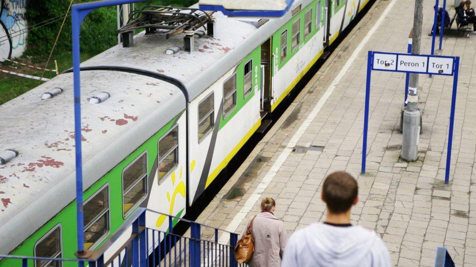 Zdjęcie pociągu osobowego stojącego na stacji kolejowej.