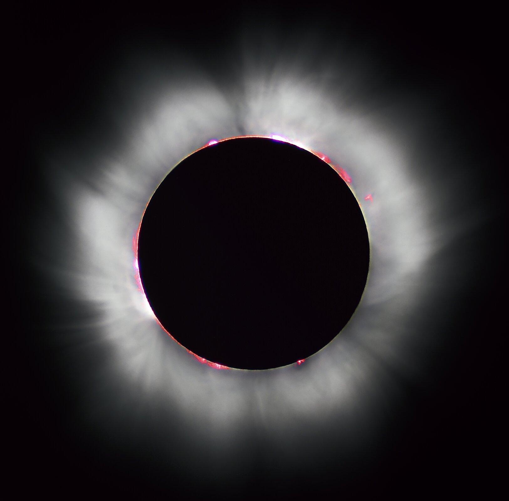 Zdjęcie przedstawia koronę słoneczną. Całe tło zdjęcia jest czarne. Wcentralnej części zdjęcia znajduje się czarne koło. Obręcz koła jest widoczna. Wokół krawędzi koła rozchodzą się świecące gazy. Gazy tworzą świetlisty obłok wokół koła. Obłok jest półprzeźroczysty. Gdzieniegdzie wokół krawędzi koła znajdują się czerwone plamy.