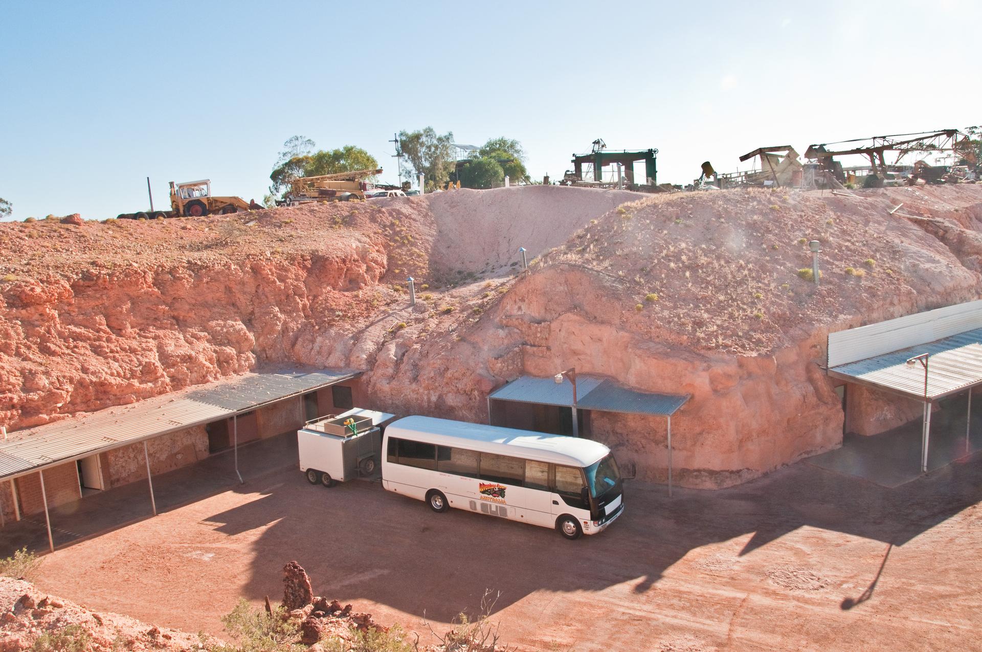 Fotografia prezentuje wyrobisko kopalni cennych kamieni. Wścianach wyrobiska znajdują się zadaszone wejścia do opuszczonych chodników kopalni. Przed jednym zwejść stoi biały autokar.