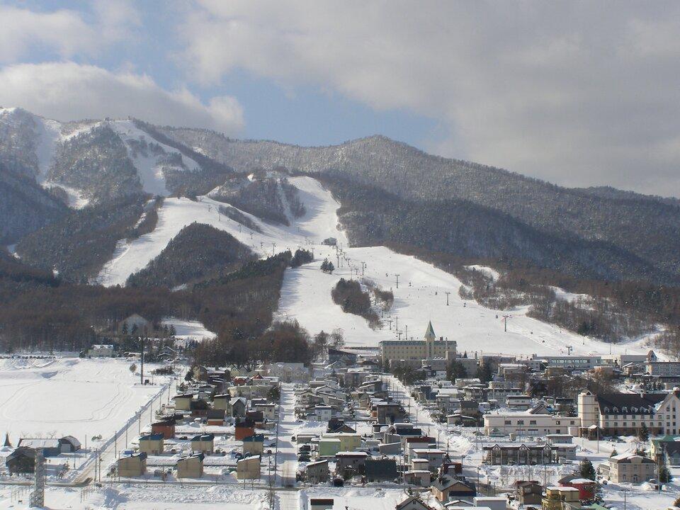 Na zdjęciu teren zabudowany położony upodnóża góry. Ośnieżone.