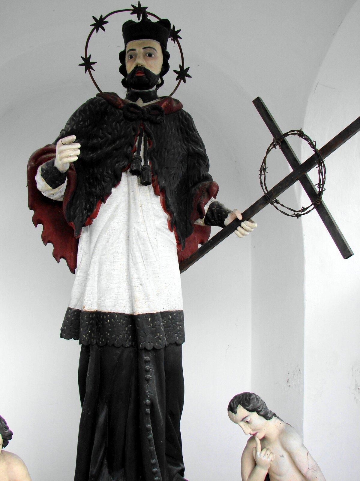 Ilustracja przedstawia figurę świętego Jana Nepomucena. Postać wdłoni trzyma krzyż. Święty ma Czarną czapkę imetalową aureolę zgwiazdkami. Brodaty mężczyzna jest ubrany wbiałą komżę, spod której wystaje czarna sutanna.