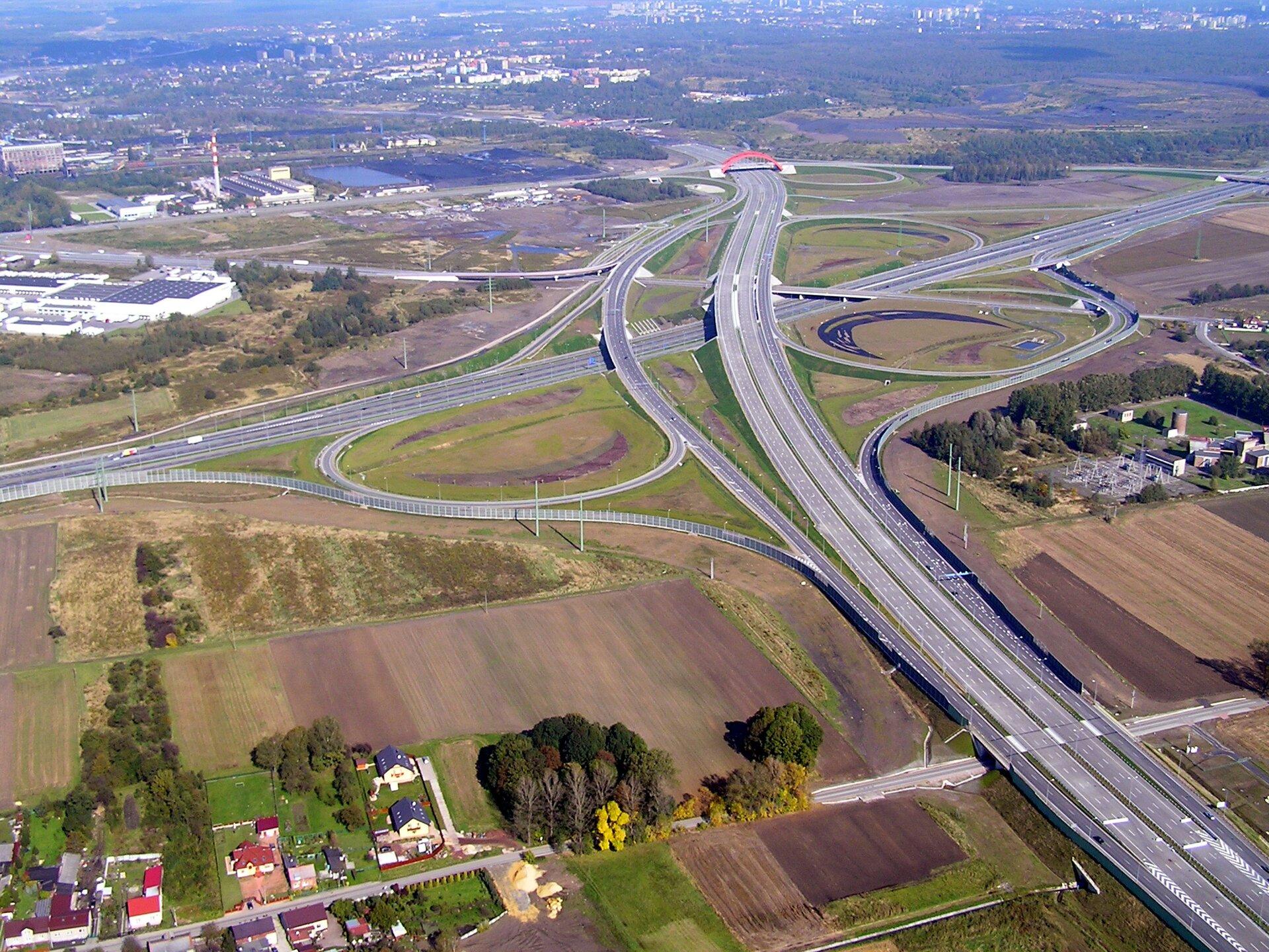 Fotografia prezentuje węzeł autostradowy umiejscowiony pomiędzy polami iłąkami.