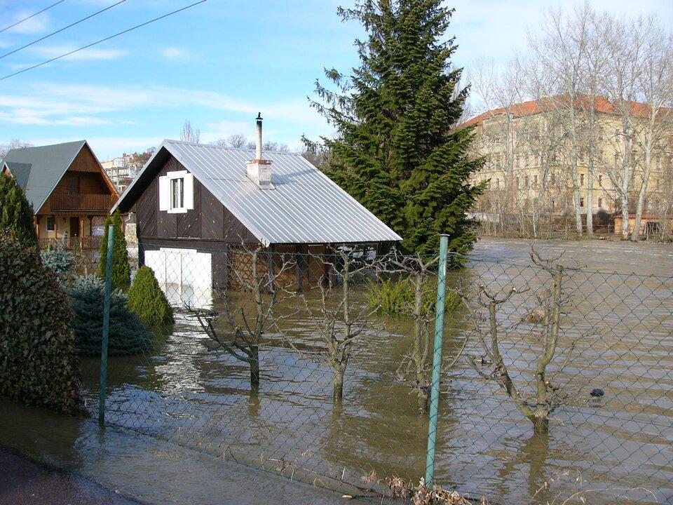 Na zdjęciu zalane podwórko przed domem, który jest ogrodzony siatką. Zwody wystają drzewa, krzewy izabudowania.