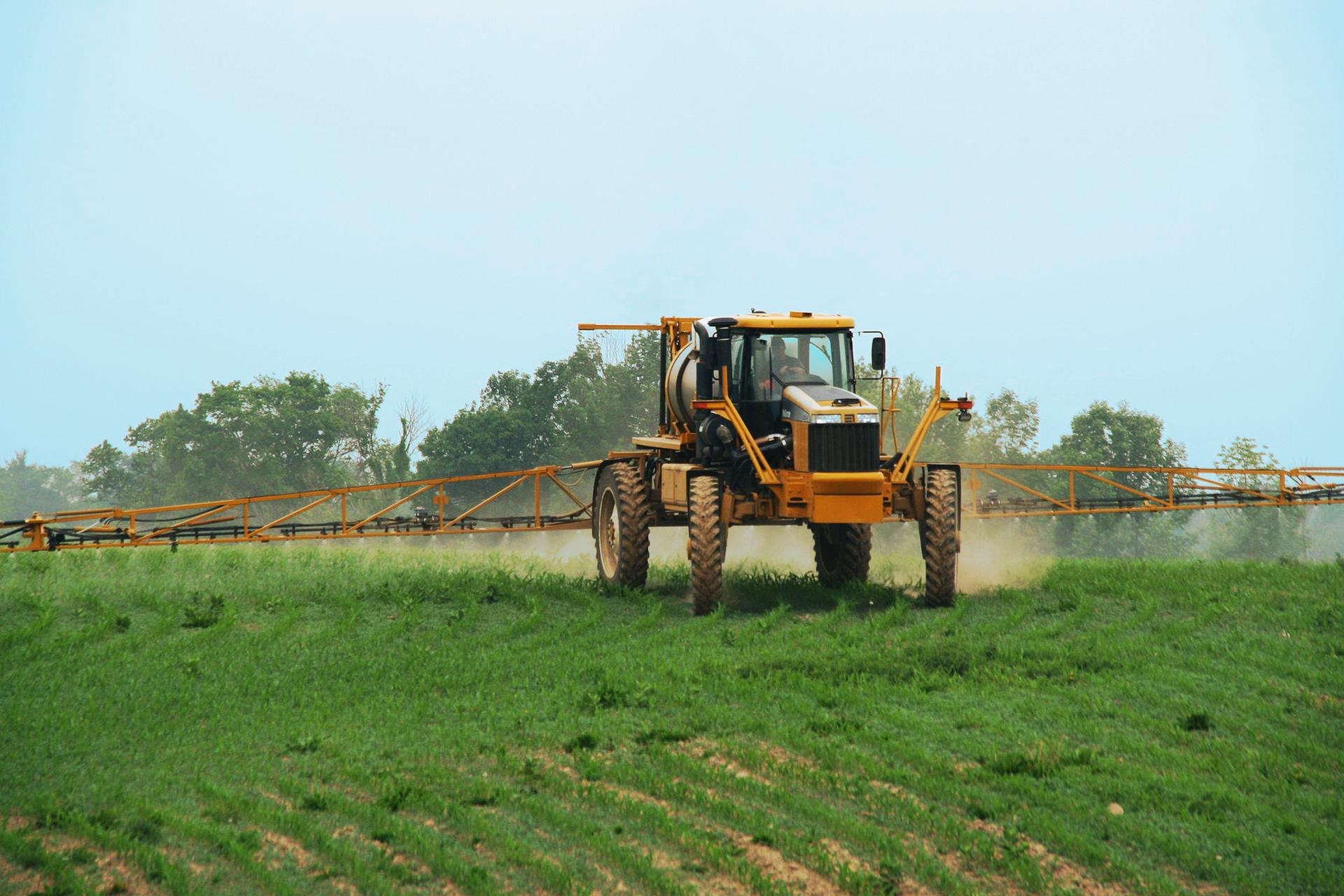 Fotografia przedstawia żółty ciągnik jadący po polu. Ztyłu traktor ma doczepione urządzenia zraszające, zktórych wykonywany jest oprysk zielonych, małych roślin na polu. Za traktorem na rośliny opada mgła zpestycydami.