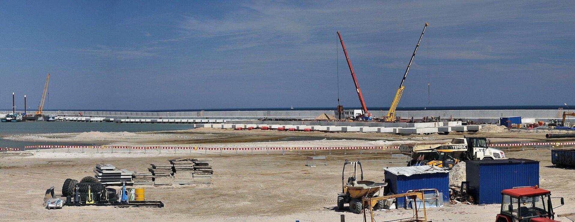 Kolorowe zdjęcie przedstawia gazoport wtrakcie budowy. Słoneczny dzień. Plaża. Na plaży elementy budowy, urządzenia, samochody, koparki. Po prawej stronie, wgłębi, dwa dźwigi. Na linii horyzontu betonowy element budowy wpostaci długiego muru zpłyt betonowych. Wgłębi zdjęcia ciemno niebieskie morze.