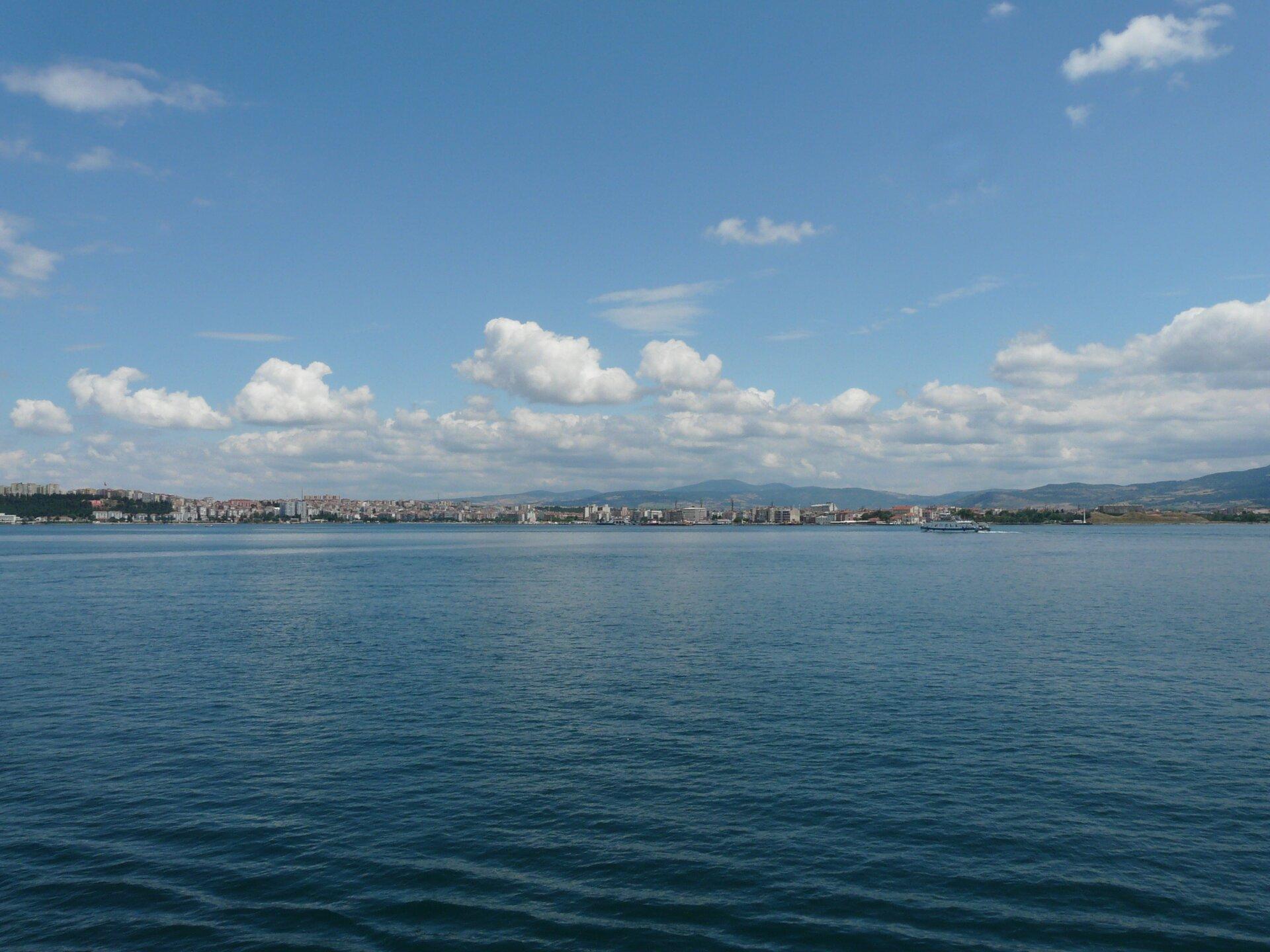 Na zdjęciu na pierwszym planie zbiornik wodny, na drugim brzegu zabudowania miejskie, wtle góry.