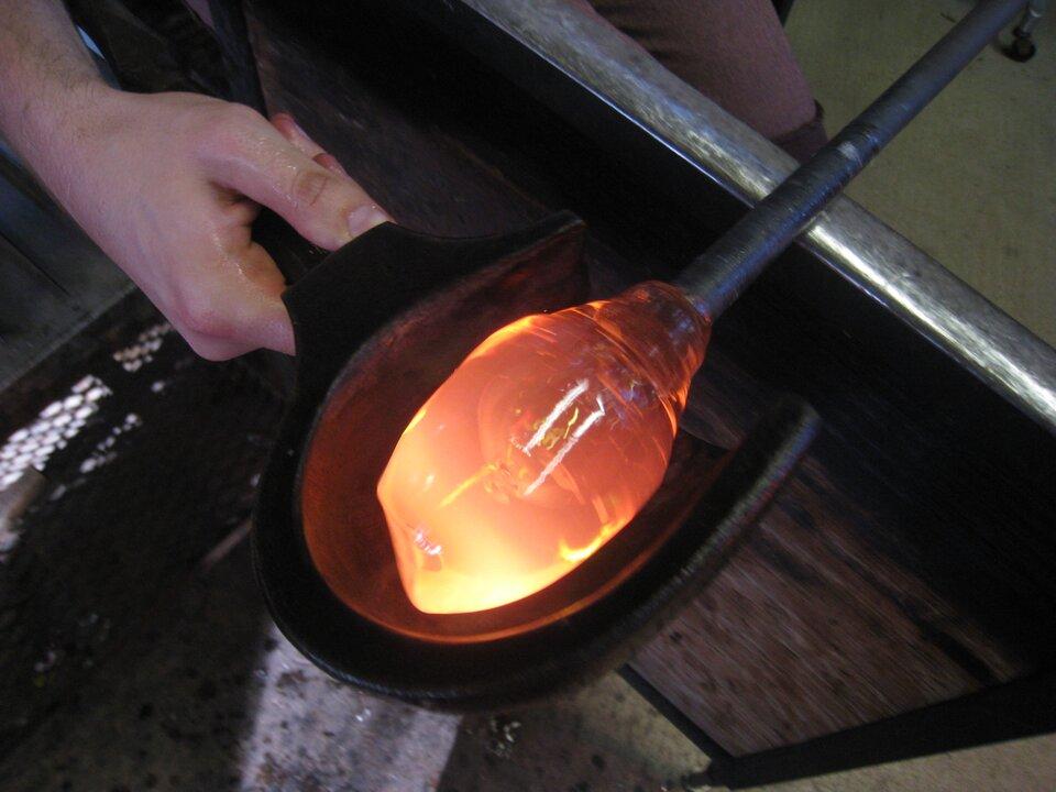 Zdjęcie przedstawia proces wytopu szkła whucie. Na zdjęciu widoczna jest dłoń pracownika. Dłoń po lewej stronie zdjęcia. Pracownik trzyma naczynie wkształcie dużej miski. Miska zakończona rączką. Nad wyżłobionym wnętrzem miski znajduje się gorący rozpalony fragment wytapianego szkła. Szkło ma kształt owalny. Bryła owalnego szkła zawieszona jest na specjalnym pręcie. Bryła szkła ma kolor żółty ipomarańczowy. Pomarańczowy bliżej pręta. Żółty występuję głównie wkońcowej części bryły.
