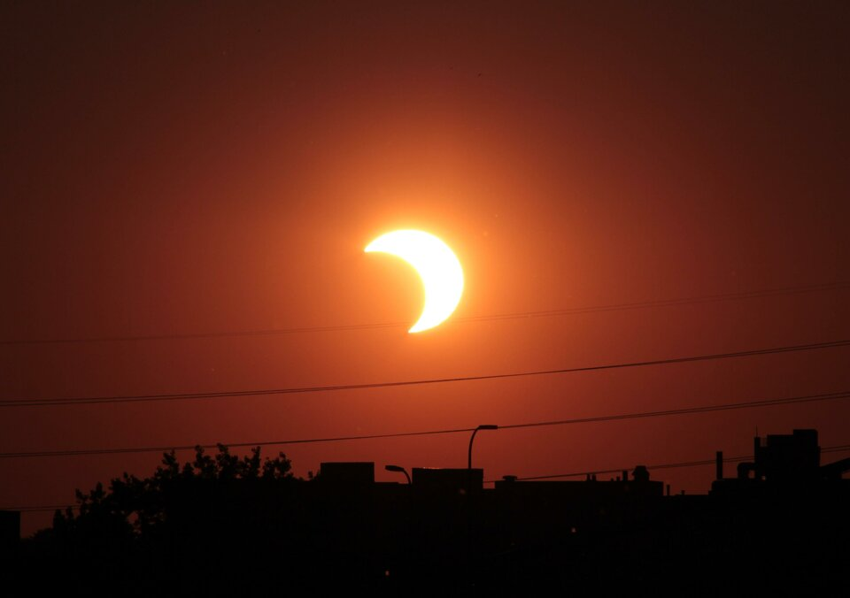 Zdjęcie przedstawia częściowe zaćmienie Słońca. Tarcza Słońca zakryta jest częściowo tarczą Księżyca, który znajduje się pomiędzy Słońcem iZiemią. Lewa strona tarczy Słońca przysłonięta Księżycem. Tarcza Słońca ma kształt półksiężyca. Półksiężyc skierowany ostrymi końcami wprawo. Wokół Słońca jasna poświata.