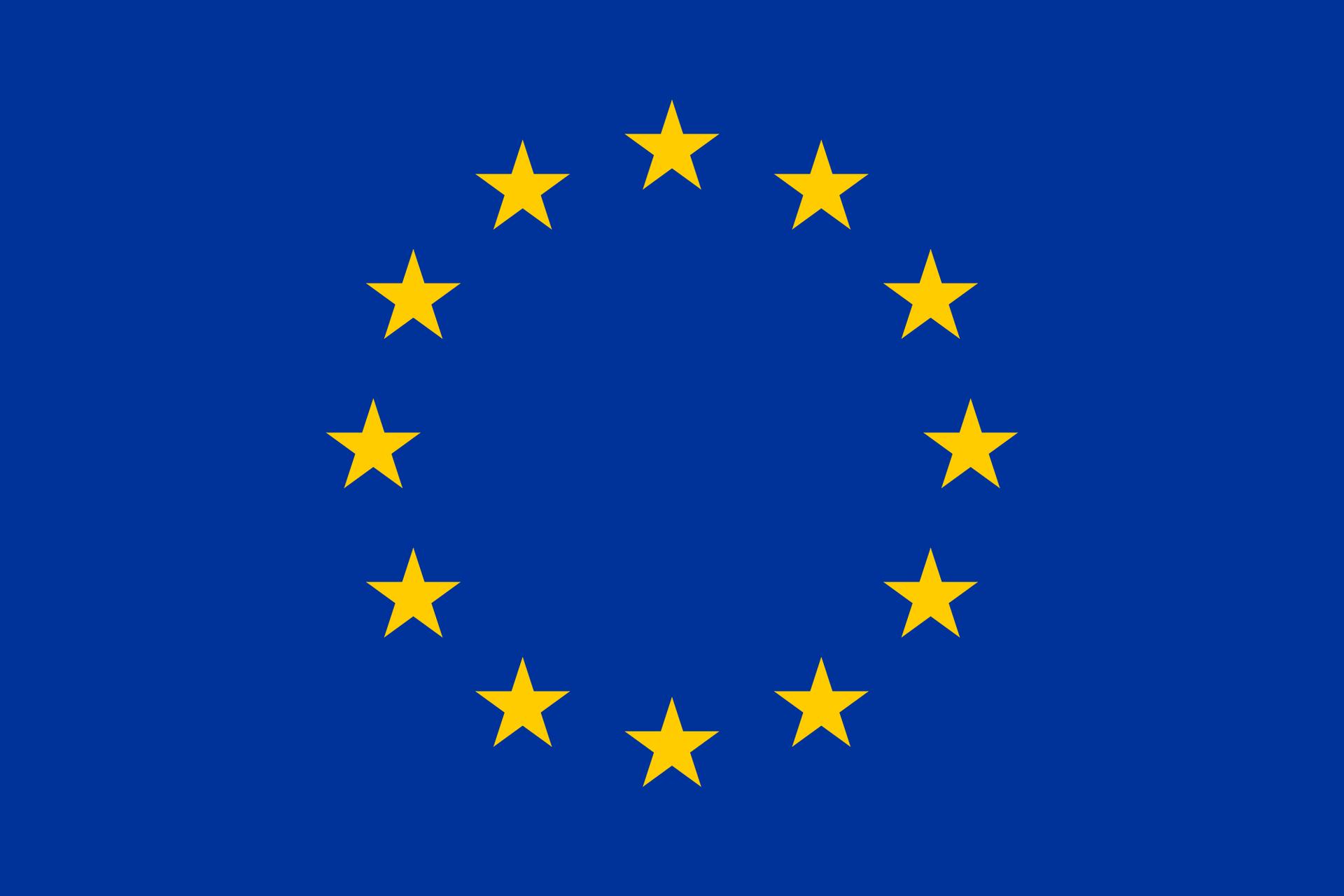 Flaga Unii Europejskiej. Na ciemnoniebieskim tle ułożonych wokrąg dwanaście pięcioramiennych, złotych gwiazd.