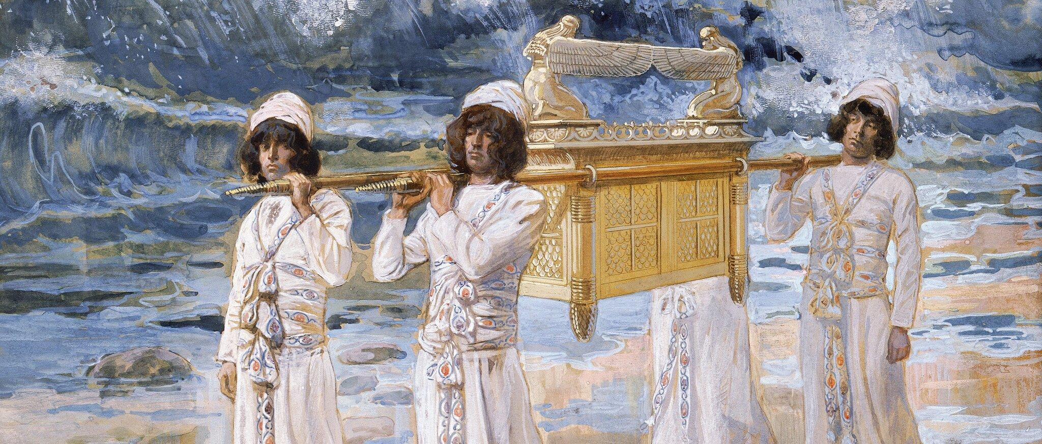 Czterej mężczyźni ubrani wbiałe szaty, zbiałymi turbanami na głowach trzymają za końca dwa drągi na których zaczepiona jest zdobiona skrzynia wkolorze złotym, na której pokrywie widać dwie rzeźby uskrzydlonych aniołów wyciągających do siebie skrzydła.