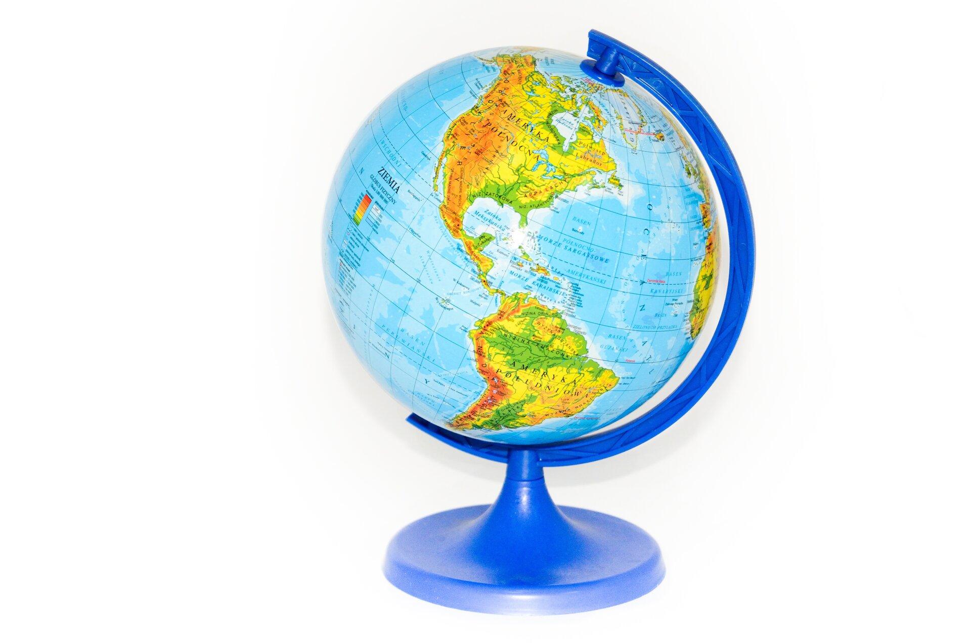 Fotografia prezentuje model Ziemi – globus. Na powierzchni globusa widoczne żółto- brązowo-zielone kontynenty otoczone niebieskimi wodami. Globus stoi na niebieskiej podstawce.