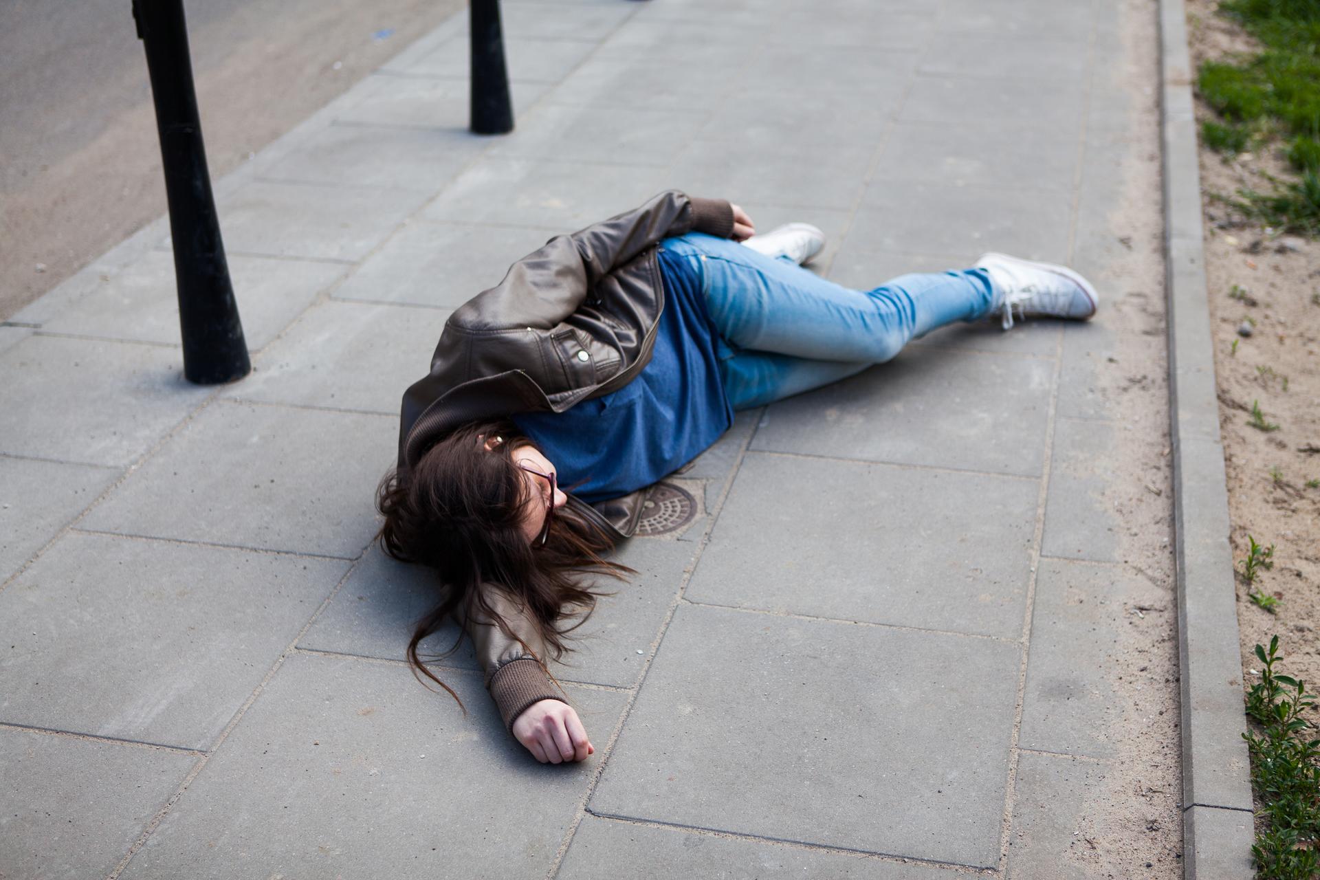 Kolorowe zdjęcie przedstawia kobietę leżącą na chodniku. Kobieta leży na boku, równolegle do krawężnika chodnika. Sylwetka usytuowana jest po prawej stronie zdjęcia. Poszkodowana ma skierowane plecy wkierunku jezdni, twarz wstronę trawnika. Głowa kobiety ułożona na wyprostowanej ręce. Druga ręka ułożona wzdłuż ciała. Dłoń na biodrach. Noga lekko zgięta do tyłu. Druga noga – wyprostowana, ułożona równolegle do dolnej kończyny. Kobieta ubrana jest wgranatowy T-shirt, dżinsy, skórzaną brązową kurtkę ibiałe buty sportowe.