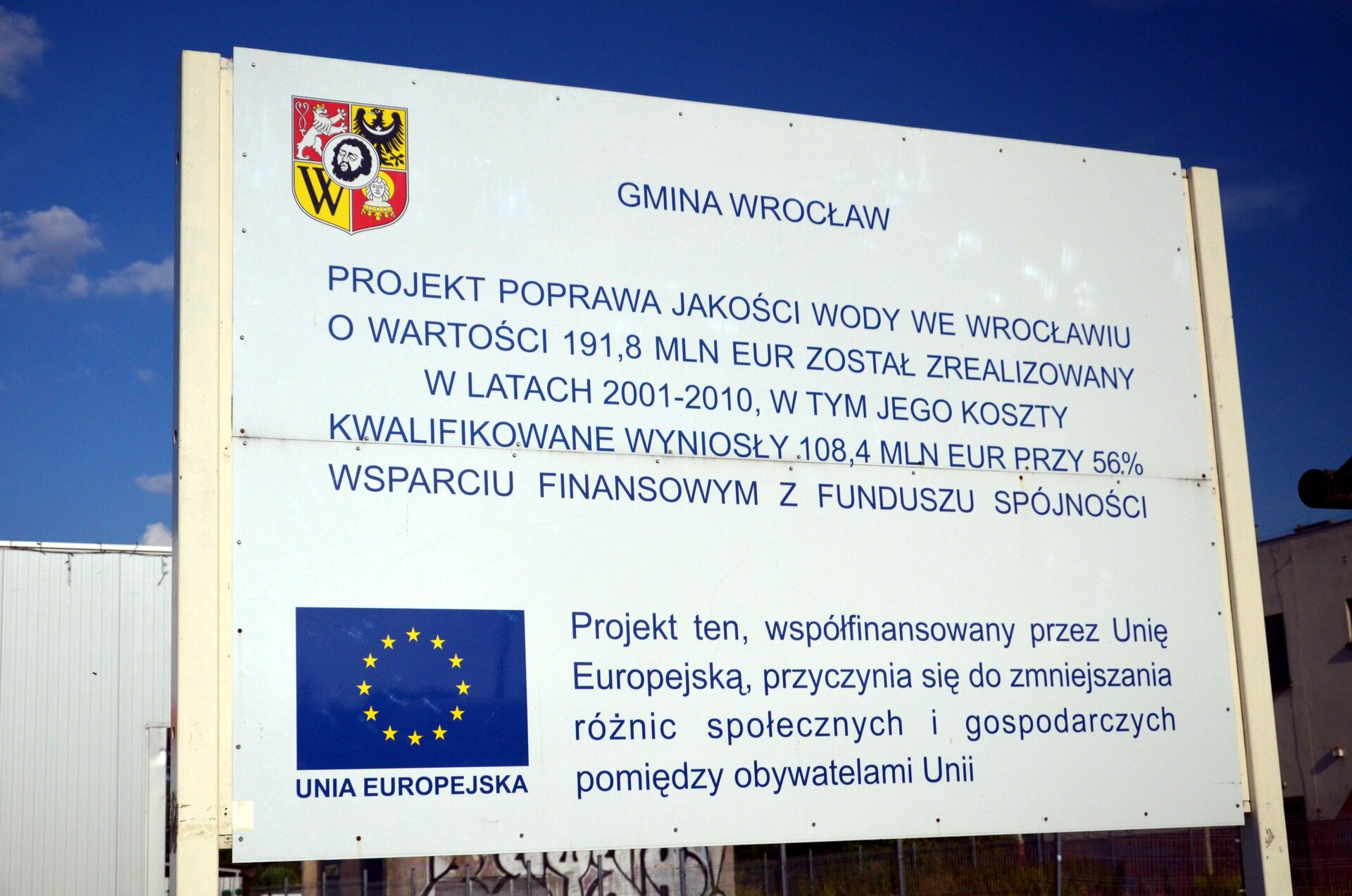 Na zdjęciu biała tablica zherbem Wrocławia iflagą Unii Europejskiej znapisem: Gmina Wrocław, projekt poprawa jakości wody we Wrocławiu owartości sto dziewięćdziesiąt jeden iosiem dziesiątych miliona euro został zrealizowany wlatach dwa tysiące jeden – dwa tysiące dziesięć, wtym jego koszty kwalifikowane wyniosły sto osiem icztery dziesiąte miliona euro przy pięćdziesięcio sześcio procentowym wsparciu finansowym zfunduszu spójności. Projekt ten, współfinansowany przez przez Unię Europejską, przyczynia się do zmniejszania różnic społecznych igospodarczych pomiędzy obywatelami Unii.