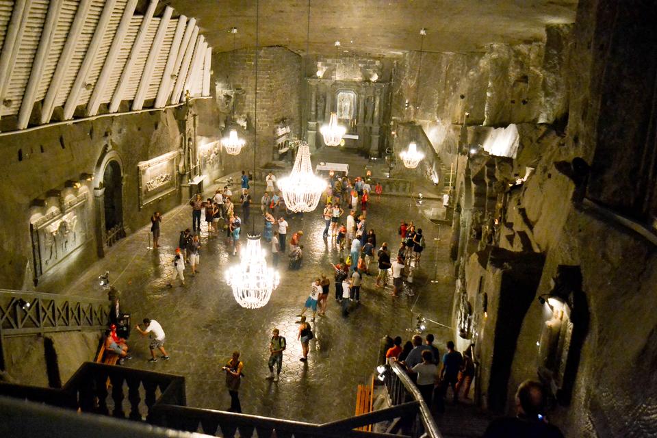 Fotografia wnętrza kaplicy św. Kingi wWieliczce. Widoczna wysoka błyszcząca sala, oświetlona przez białe kryształowe żyrandole . Wkaplicy znajdują się liczne osoby ją zwiedzające.
