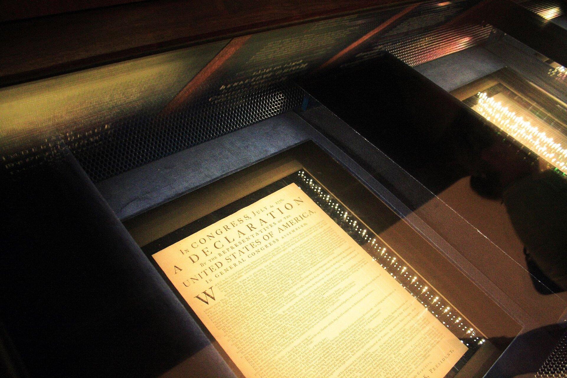 Ilustracja przedstawia zdjęcie Deklaracji Niepodległości Stanów Zjednoczonych przechowywanej wszczelnie zamkniętej oszklonej gablocie. Dokument jest oświetlony otaczającymi go paskami diod LED wcelu umożliwienia jego łatwego odczytania przez kilka warstw szkła.