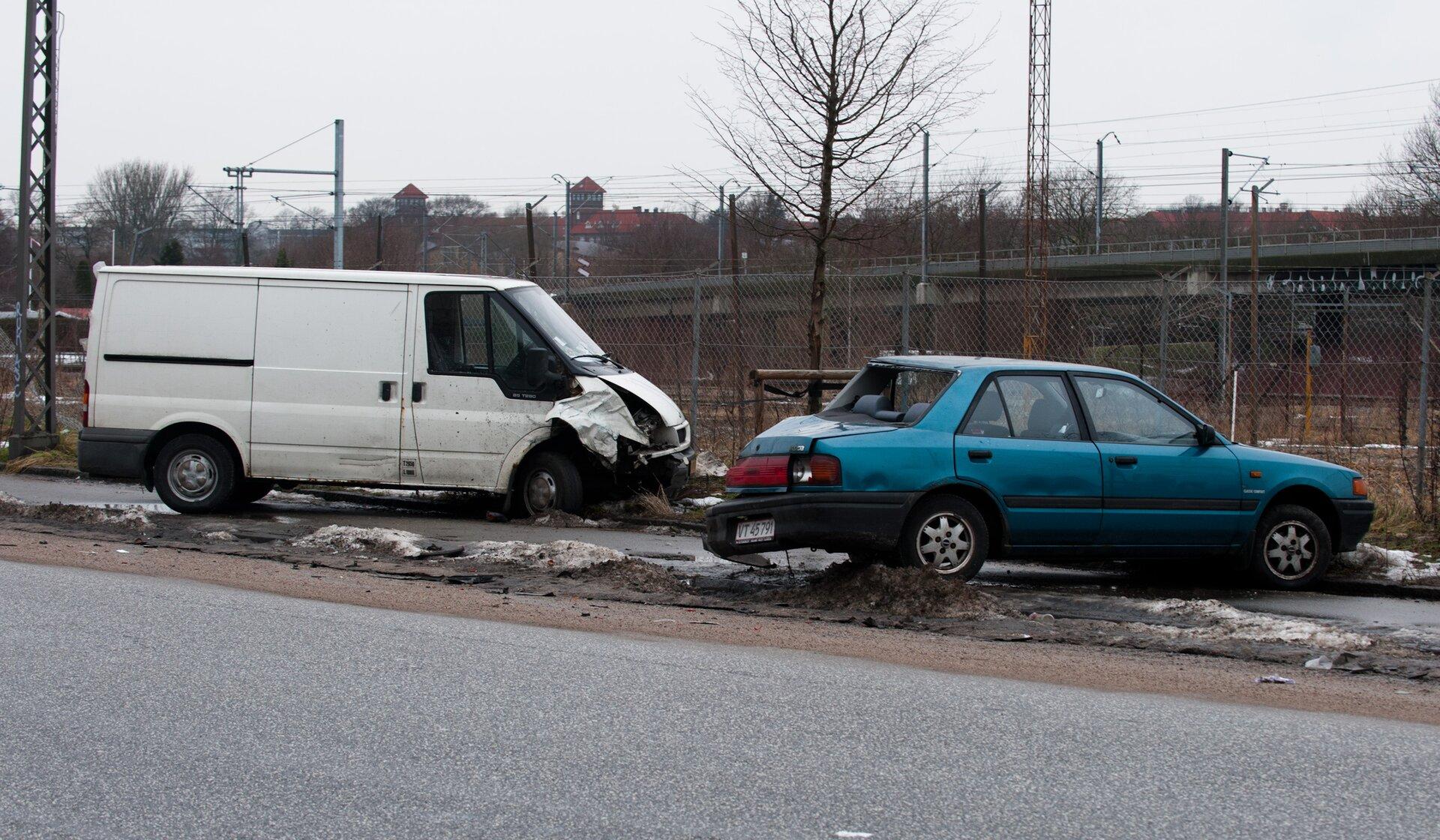 Zdjęcie przedstawia wypadek drogowy wmiesiącach zimowych lub wtrakcie przedwiośnia, na co wskazują resztki śniegu na drodze. Na pierwszym planie, wdole zdjęcia, asfaltowa ulica. Za ulicą, na poboczu, dwa rozbite auta. Po lewej stronie kadru mniej więcej równolegle do ulicy stoi biała furgonetka. Rozbity przód furgonetki znajduje się wcentrum kadru, podobnie jak rozbita tylna część niebieskiego samochodu osobowego. Furgonetka ma zniszczone prawe przednie nadkole imniej więcej połowę maski, atakże uszkodzone boczne lusterko. Samochód osobowy, stojący na prawo od furgonetki został uderzony wtył, ma wybitą tylną szybę, rozbite tylne światła ioderwany zlewej strony zderzak. Pojazd stoi wpoprzek chodnika.