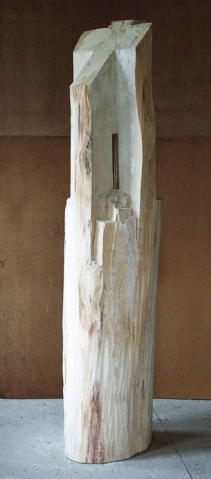 """Ilustracja przedstawia rzeźbę Krzysztofa Mazura """"Kapliczka biała"""". Jest to drewniany, ciosany pień drzewa ukształtowany wbryłę zbliżoną do walca, wgórnej części kaskadowo pościnanego. Wśrodku pień jest wydrążony - zawiera wąski prześwit. Górna część tworzy krzyż."""