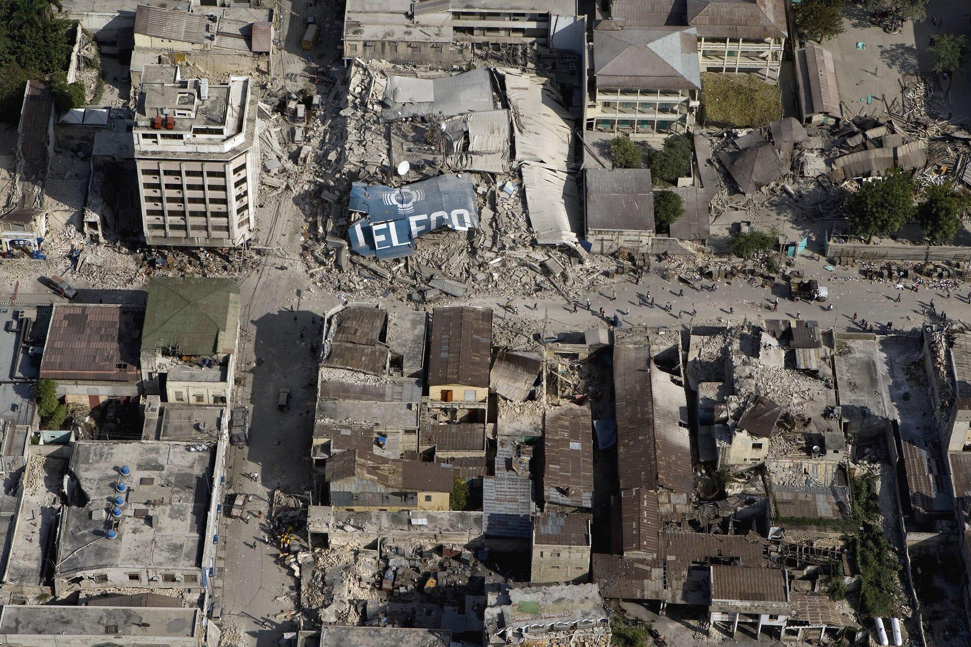 Zdjęcie przedstawia skutki trzęsienia ziemi oglądane zlotu ptaka. Słoneczny dzień, miasto Port-au-Prince, stolica Haiti w2010 roku. Całe zdjęcie zajmują ruiny budynków mieszkalnych po trzęsieniu ziemi. Wpołowie zdjęcia, główna ulica sięga lewej iprawej krawędzi zdjęcia. Na ulicy mieszkańcy miasta. Wzdłuż ulicy, udołu zdjęcia oraz zprawej strony również ugóry, brązowe blaszane dachy ocalałych domów. Ulica częściowo zasypana gruzem zniszczonych budynków wcentrum kadru. Wdolnej połowie zdjęcia budynki są niskie. Wgórnej części zdjęcia ocalałe budynki to bloki mające po pięć lub sześć pięter. Ściany betonowych bloków białe bez widocznych pęknięć.