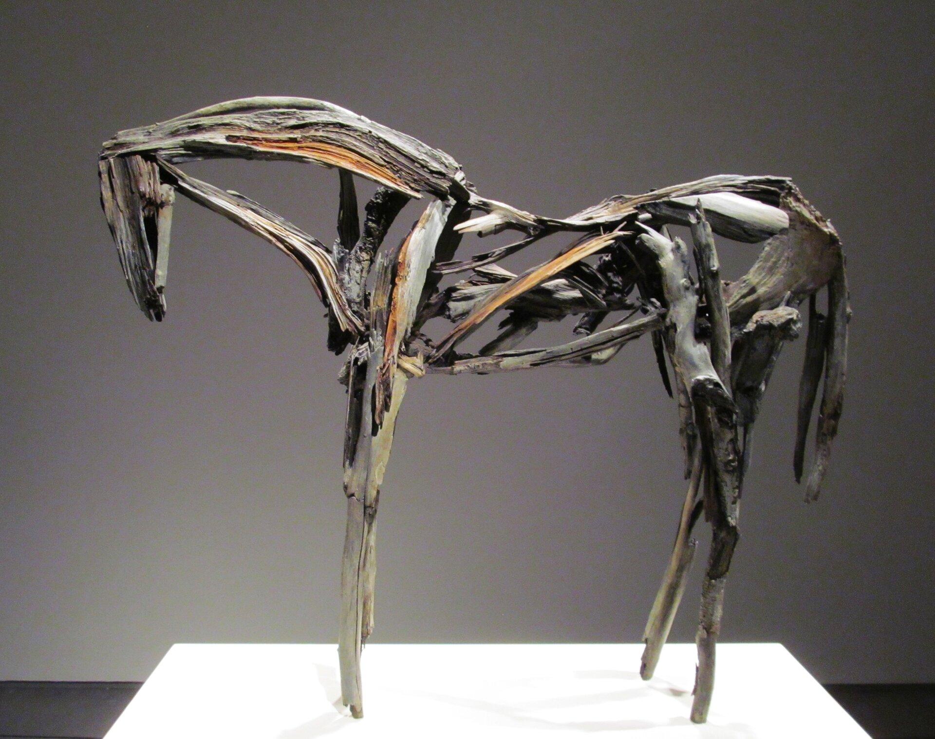 """Ilustracja przedstawia rzeźbę """"Koń"""", wykonaną przez Deborah Butterfield. Jest to konstrukcja konia stojącego ze zwieszonym łbem, pozbawiona pełnowymiarowości, zbudowana ze szkieletu, który artystka wykonała najpierw zgliny ipatyków, anastępnie odlała zbrązu. Szkielet jest spatynowany. Rzeźba ustawiona jest na płaskiej, białej podstawie."""