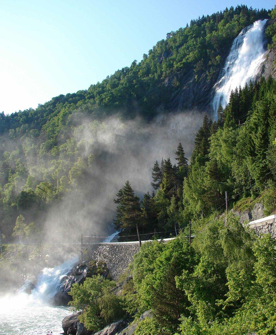 Na zdjęciu wodospad spadający ze stromego porośniętego lasem wzgórza. Wdole droga pokryta mgłą utworzoną ustóp wodospadu. Wąska struga wody przepływa pod drogą iwpada do zbiornika wodnego na pierwszym planie.