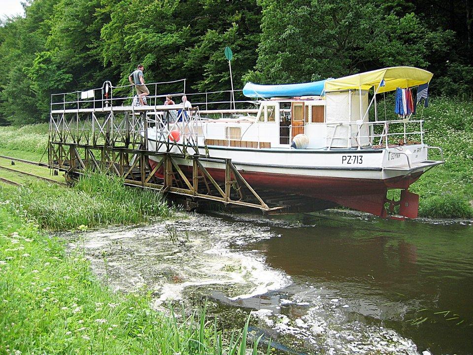 Fotografia prezentuje pochylnię na Kanale Elbląskim. Widoczny statek umieszczony na platformie, która jedzie po szynach.