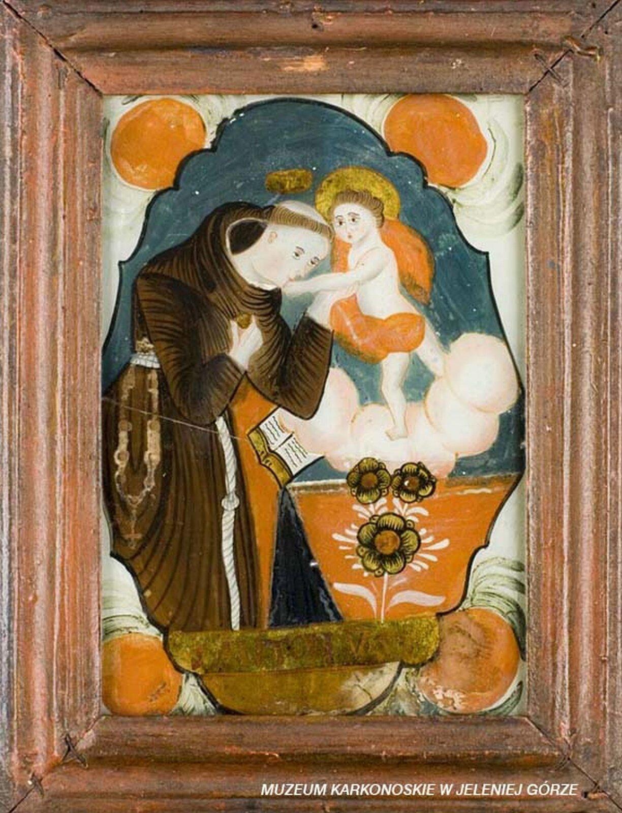 Ilustracja przedstawia malowidło na szkle, które ukazuje św. Antoniego. Zakonnik ubrany jest whabit przewiązany sznurem. Uboku przewieszony ma różaniec. Całuje wrękę stojącego na chmurze małego Jezusa. Na dole znajdują się kwiaty.