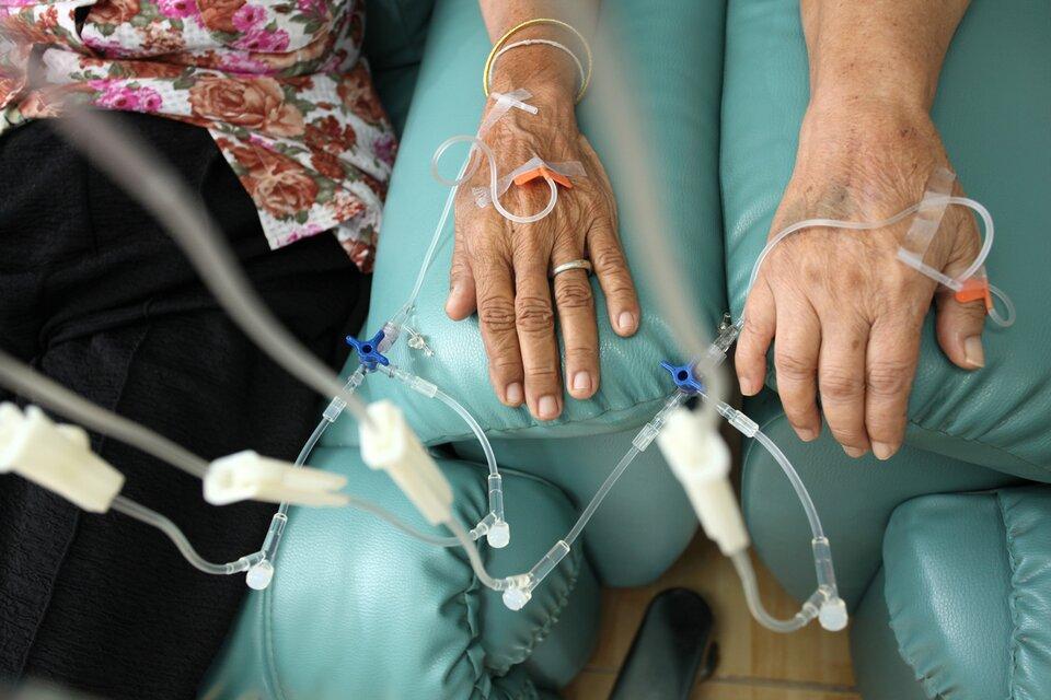 Ilustracja przedstawia dłonie dwojga chorych. Do ich żył podawana jest kroplówka zlekiem antynowotworowym.
