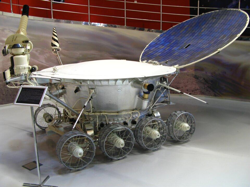 Zdjęcie przedstawia radziecki łunochod. Maszyna wygląda jak duży, srebrny pojemnik wkształcie balii, umieszczony na ośmiu kołach. Łunochod zzewnątrz posiada wiele mniejszych podzespołów, przewodów itym podobne. Ztyłu umieszczono element, który wygląda jak antena satelitarna. Powierzchnia elementu składa się zdrobnych niebieskich, granatowych ibrązowoszarych prostokątów. Łunochod umieszczono na szarym podłożu.