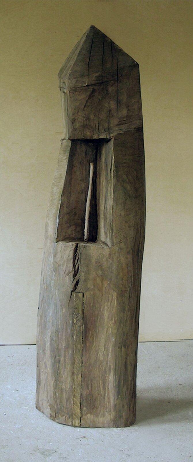 """Ilustracja przedstawia rzeźbę Krzysztofa Mazura """"Kapliczka frasobliwa"""". Jest to drewniany, ciosany pień drzewa ukształtowany wbryłę zbliżoną do walca, zwieńczonego stożkiem. Górna część jest lekko pochylona. Wśrodku pień jest wydrążony. We wnęce znajduje się wmontowany jasny patyk."""