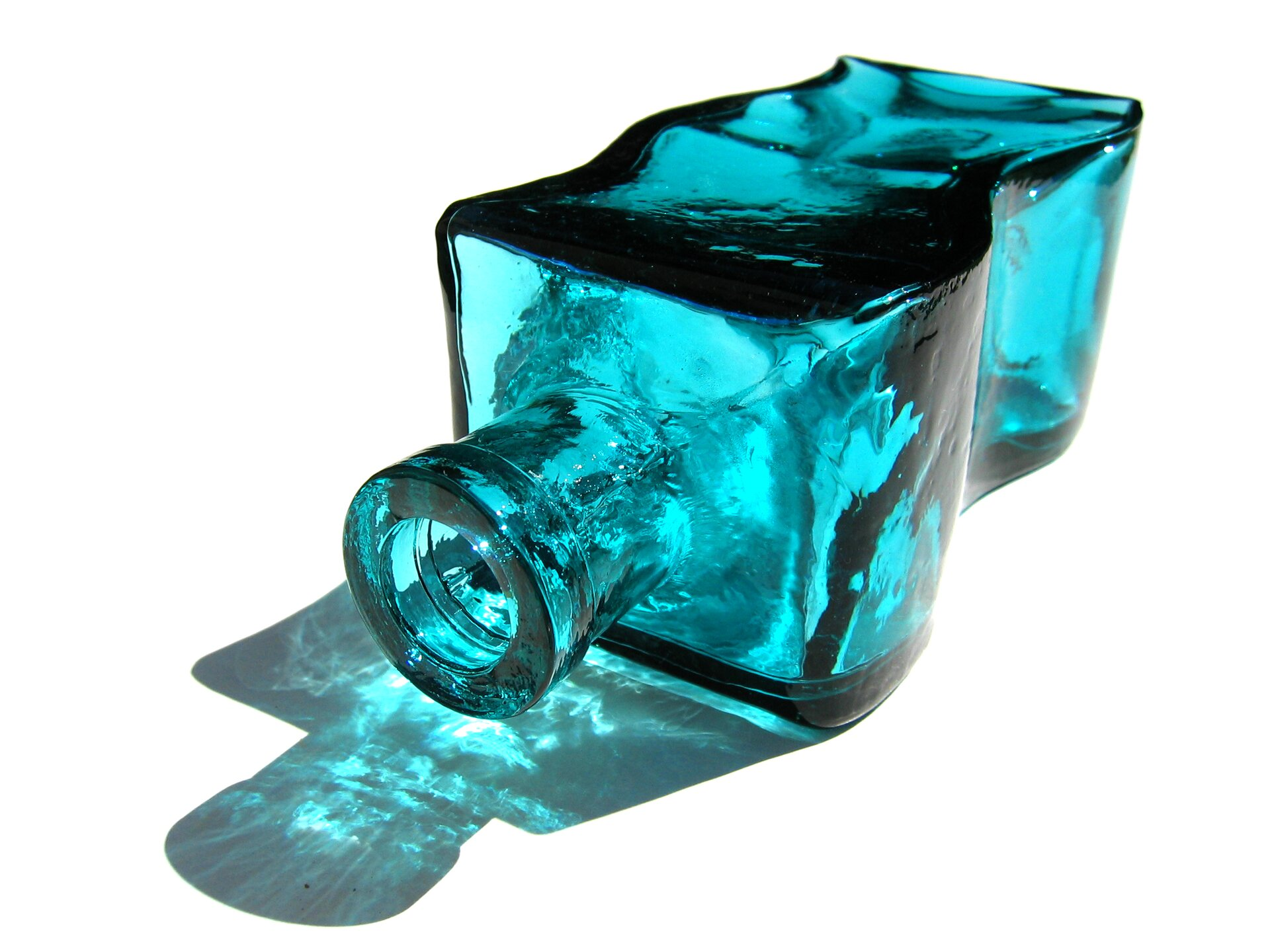Zdjęcie przedstawia ozdobną butelkę zgrubego, niebieskiego szkła. Butelka ma kształt pofalowany ileży na boku, na białej, płaskiej powierzchni.