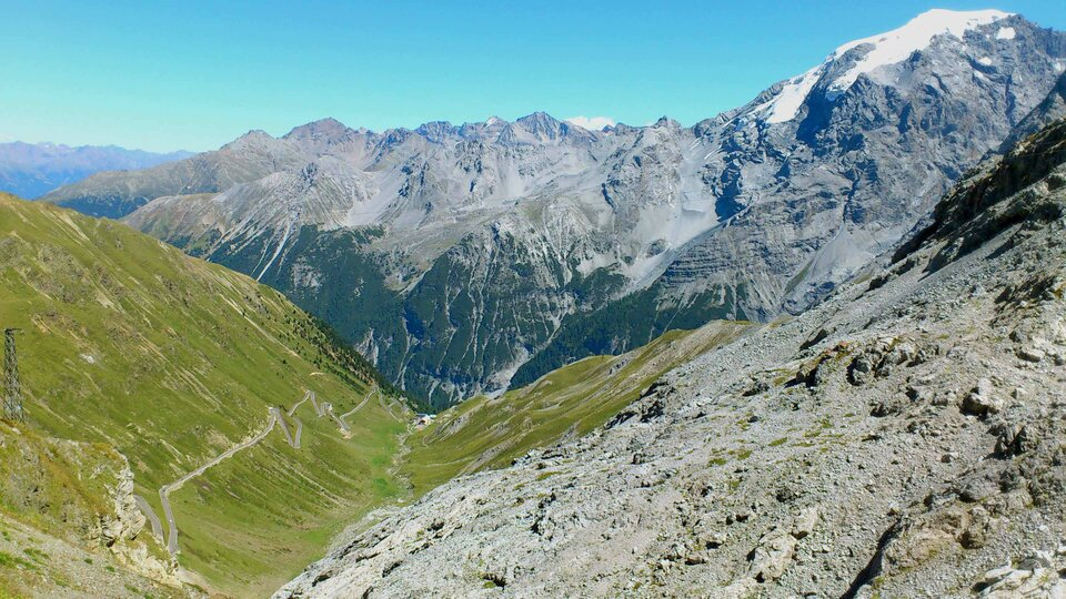 Na zdjęciu pasmo górskie. Odsłonięte stoki pozbawione roślinności, niżej zadrzewione, szczyty pokryte gdzieniegdzie śniegiem. Na pierwszym planie dolina porośnięta trawą. Droga odużej ilości zakrętów.