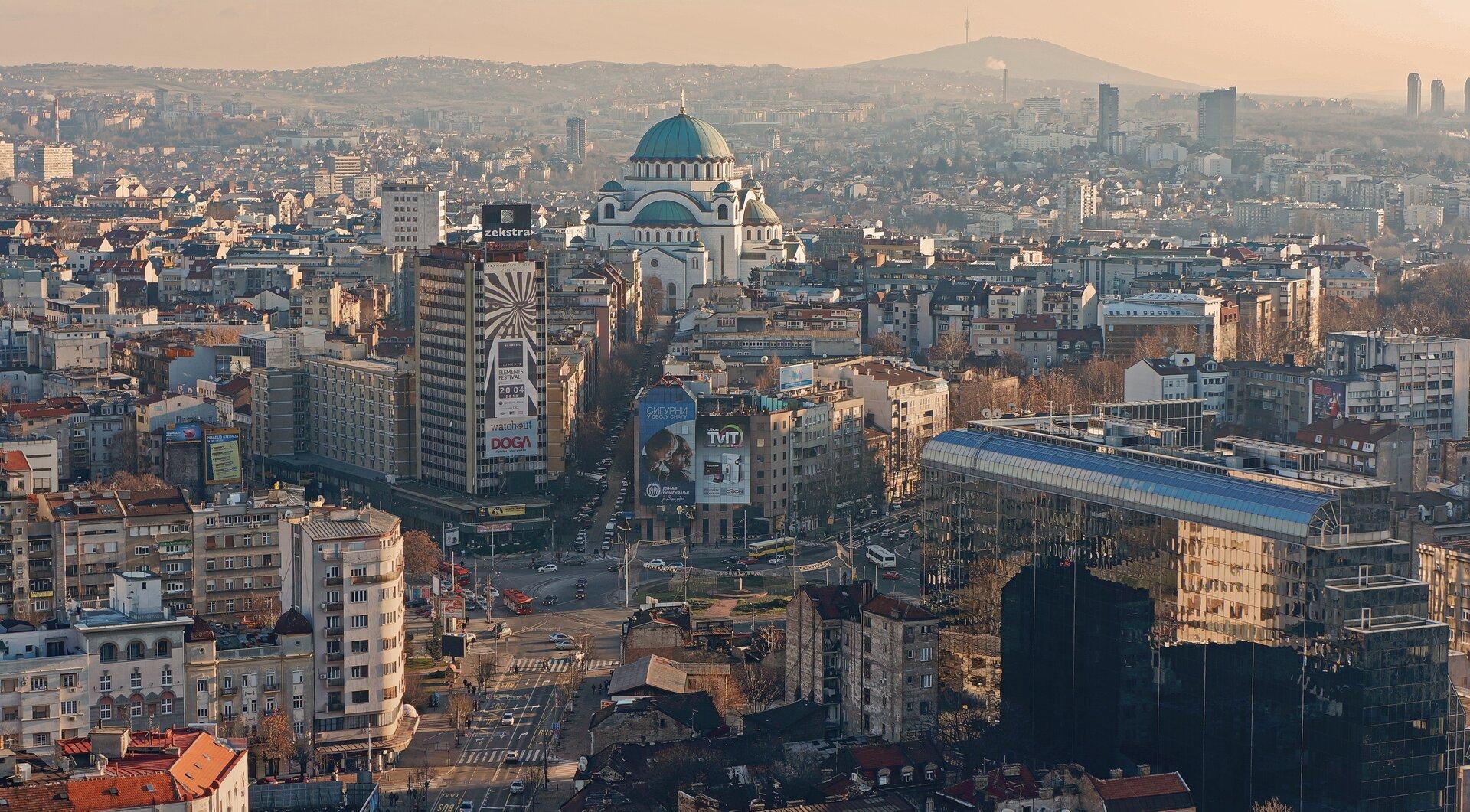 Na zdjęciu Belgrad, zwarta zabudowa miejska, budynki ustawione bardzo gęsto, środkiem przebiega ulica, rondo. Wtle szczyt góry.