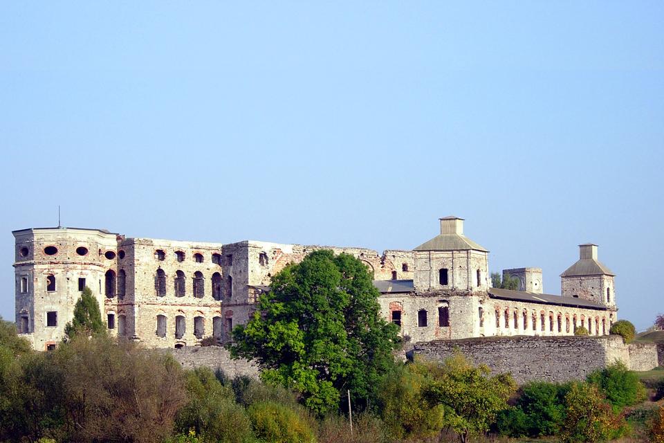 Fotografia prezentuje ruiny ogromnego zamku Krzyżtopór. Widoczne mury zamku otoczone murem obronnym. Poniżej muru rosną liczne drzewa.