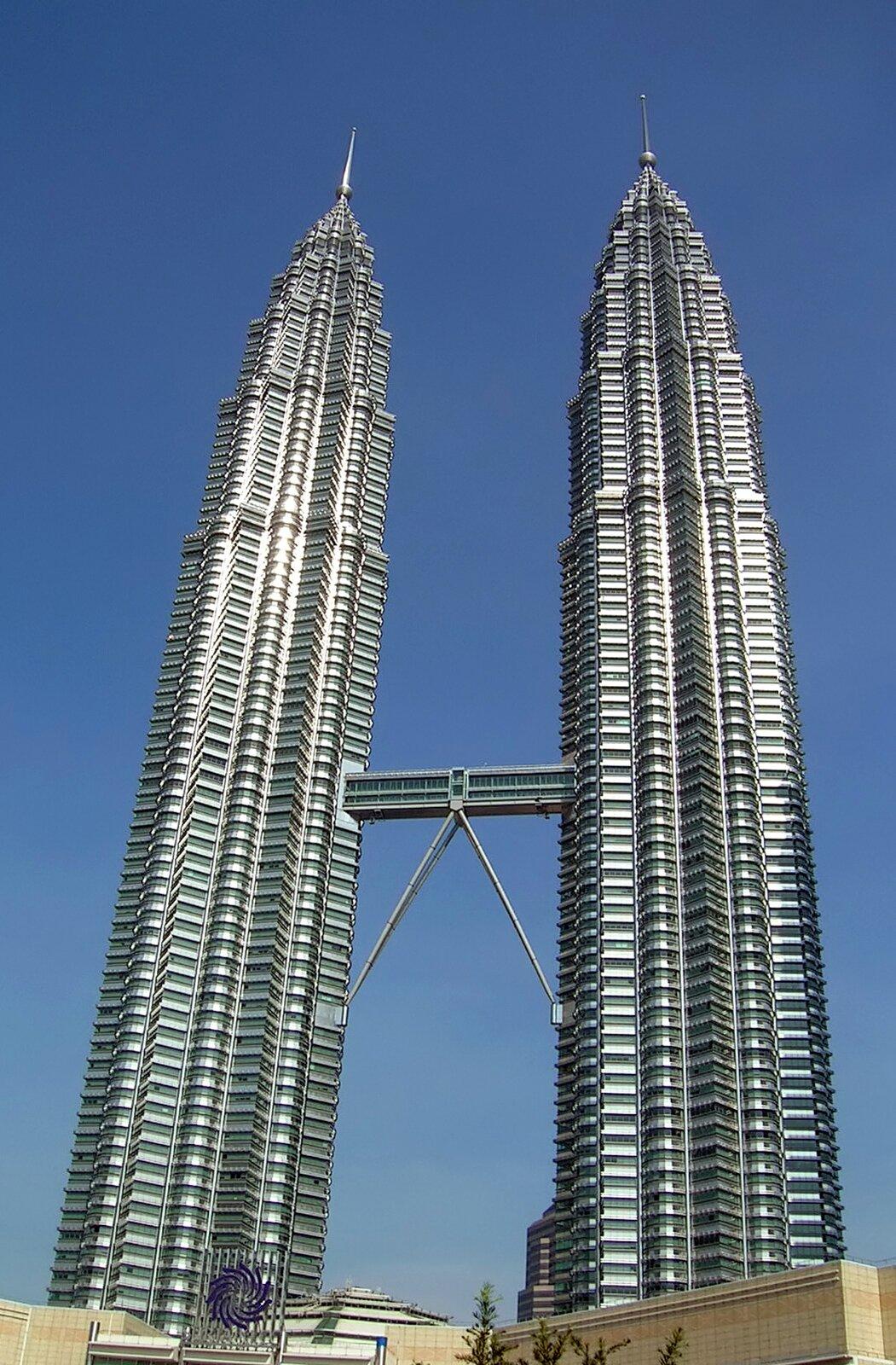 Zdjęcie przedstawia budynek Petronas Towers wKuala Lumpur, bliźniaczych wież owysokości 452 metrów. Oszklone drapacze chmur połączone są mostem odługości prawie sześćdziesięciu metrów na poziomie 41 i42 piętra.